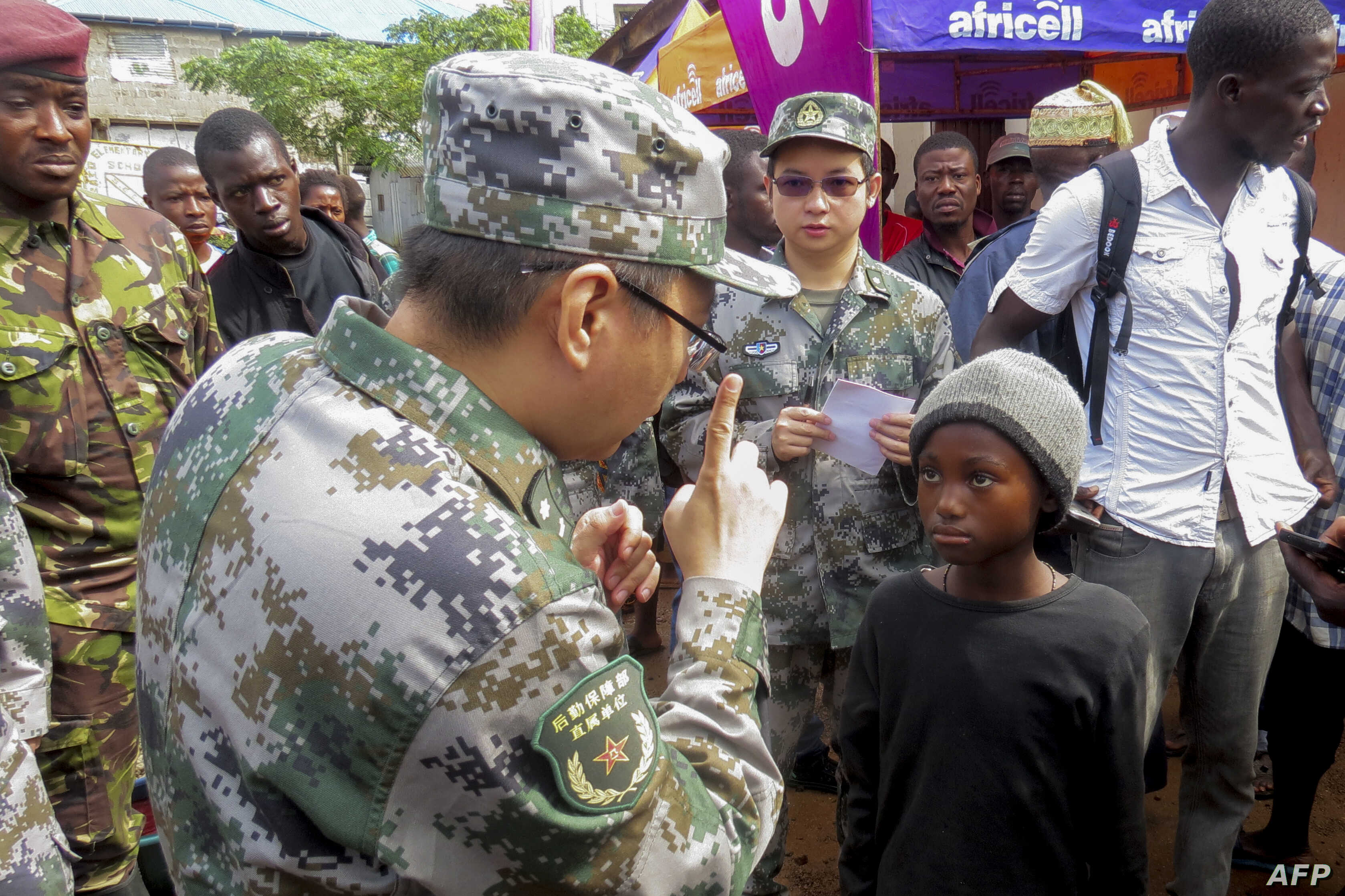 FILE - A medical team from the Chinese People's Liberation Army (PLA) meets with local Sierra Leoneans as they arrive close to the site of a mudslide in Sugar Loaf mountain, in Freetown, Aug. 17, 2017.