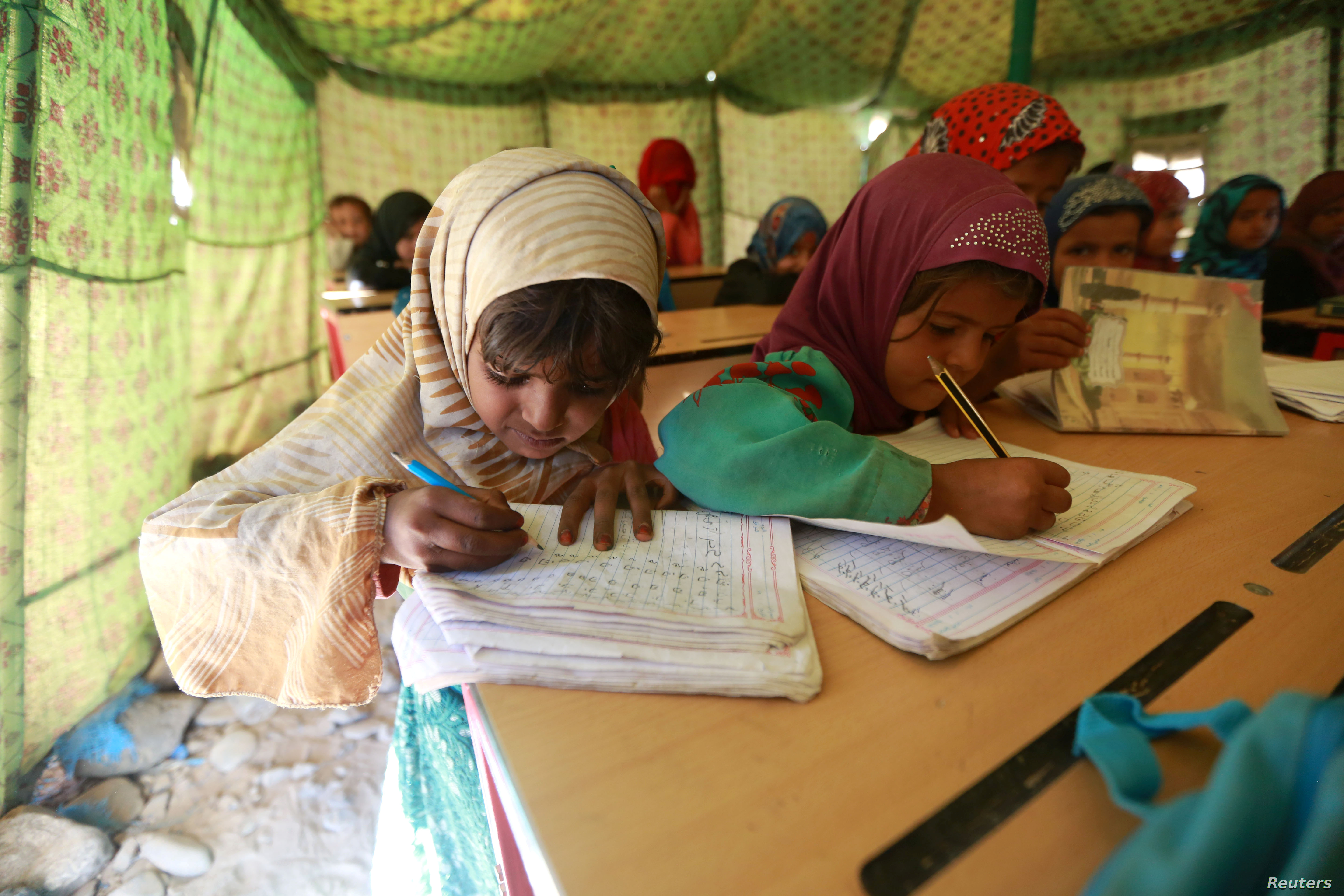 Displaced Yemeni students attend a class in a tent at a refugee camp located between Marib and Sanaa, Yemen, March 29, 2018.