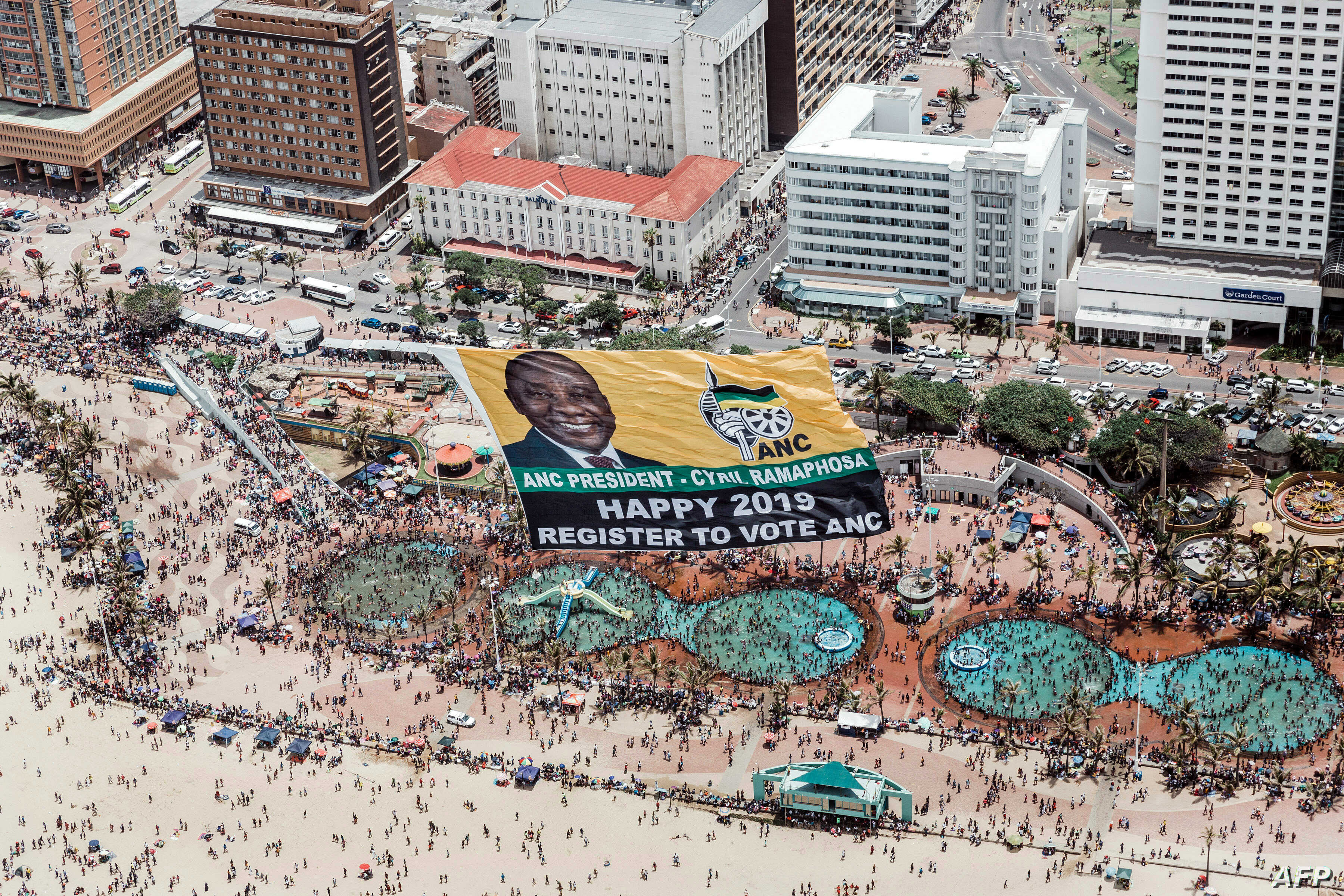 An aerial view shows a helicopter flying a giant flag of the South Africa's ruling African National Congress (ANC) displaying a picture of South African President Cyril Ramaphosa and urging people to register to vote for upcoming elections.
