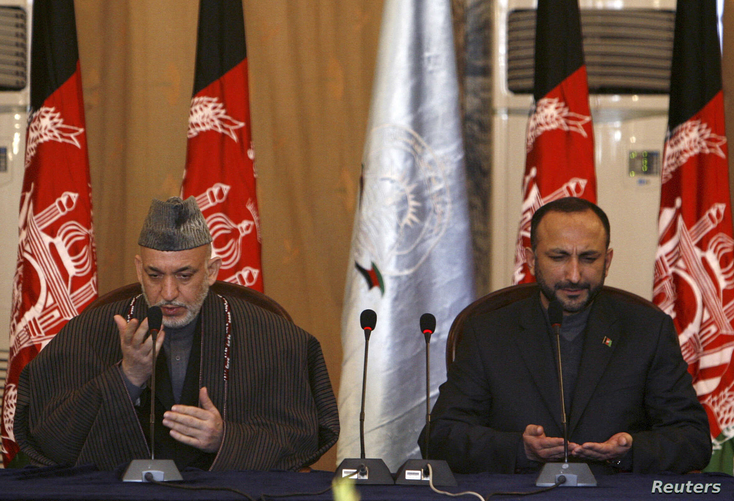 Former Afghan president Hamid Karzai, left, and former national security adviser Haneef Atmar, seen here offering prayers at a forum in forum in Kabul, Feb. 12, 2008, are among influential Afghans expected to attend the Moscow talks.