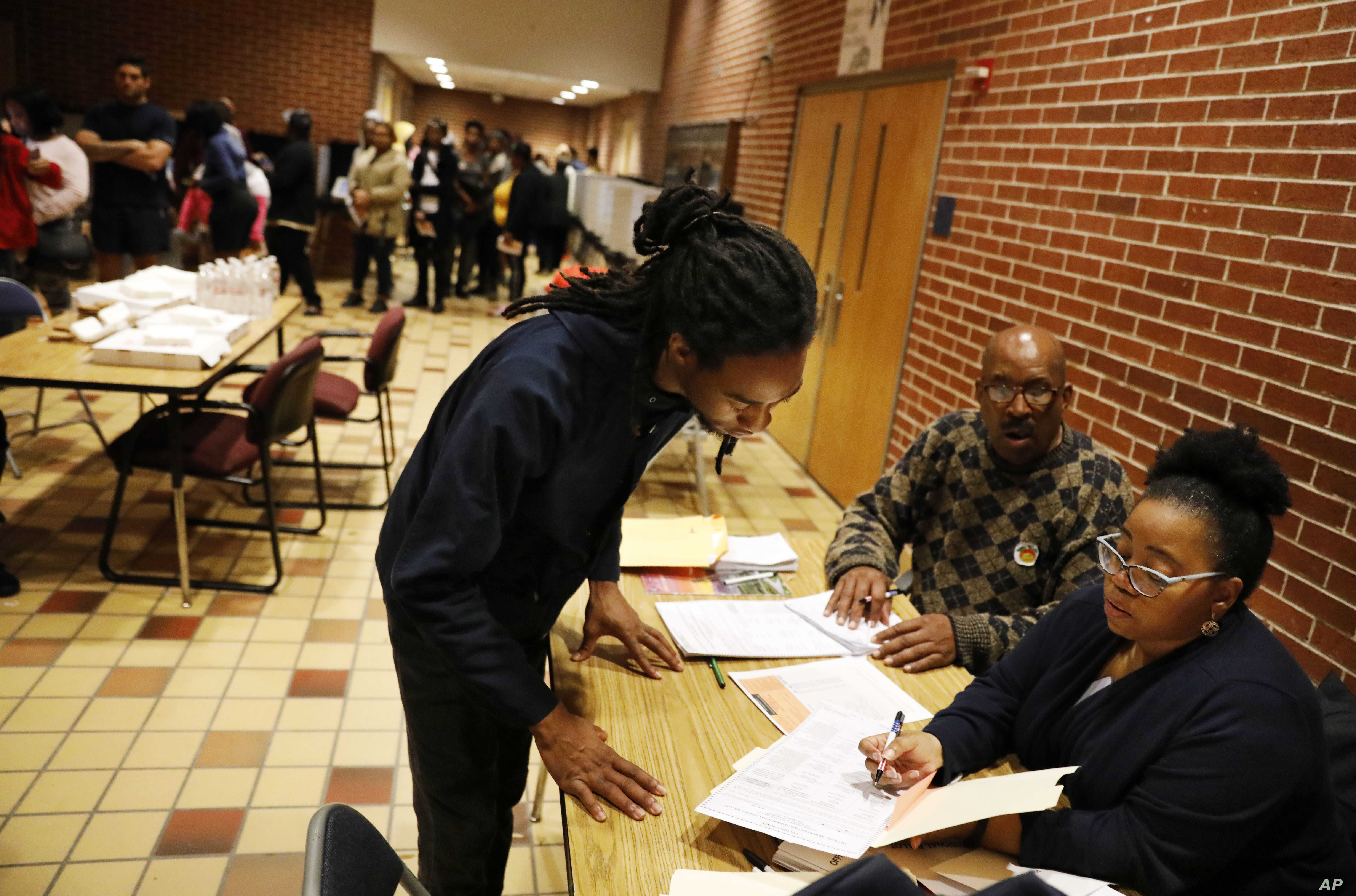 Sebastian Snelling, left, is given instructions on using a paper ballot as the precinct switched over from electronic voting machines after a judge ordered the location to stay open until 10 p.m., in Atlanta, on Nov. 6, 2018.