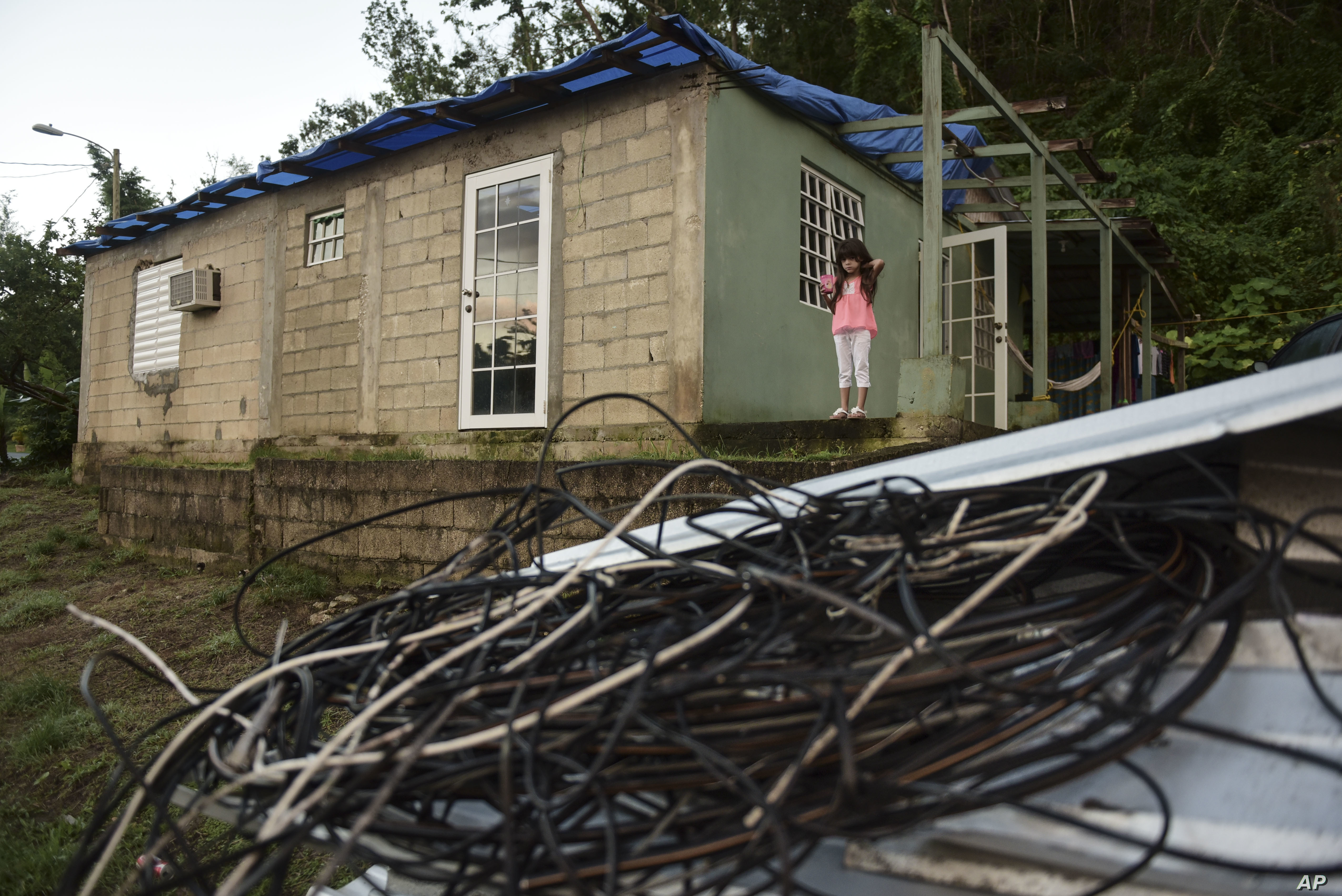 Melanie Oliveras González, 6,  stands on the porch of her house, in front of a handful of electric cables knocked down by the winds of Hurricane Maria, in Morovis, Puerto Rico, Dec. 22, 2017. Morovis has been without power since hurricane smashed in...