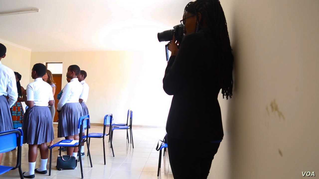 Gloria Iribagiza snaps photos in a classroom. (Photo: C. Oduah for VOA)