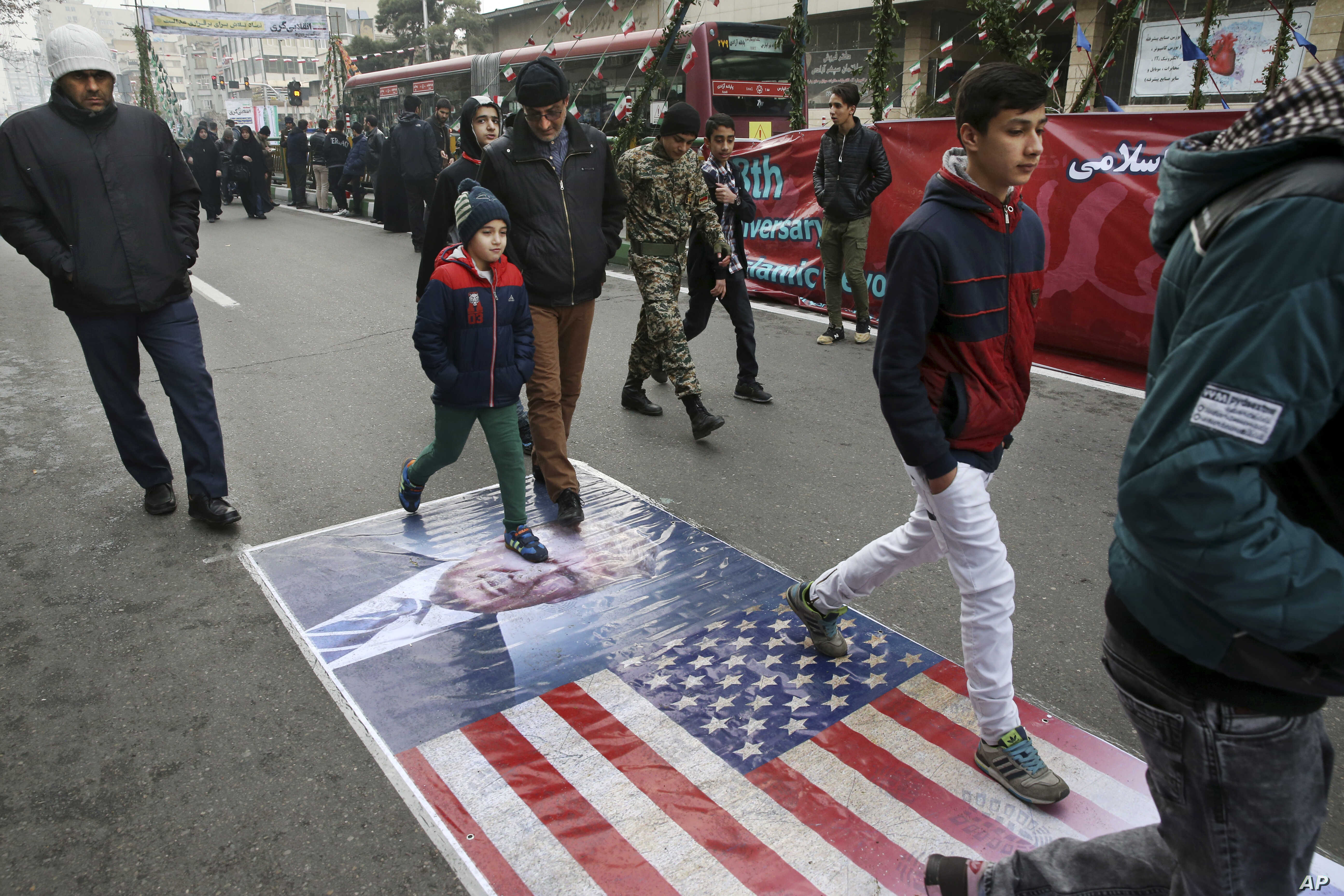 Iranians march on a portrait of U.S. President Donald Trump and the picture of U.S. flag in an annual rally commemorating the anniversary of the 1979 Islamic revolution, which toppled the late pro-U.S. Shah, Mohammad Reza Pahlavi, in Tehran, Iran, Fe...