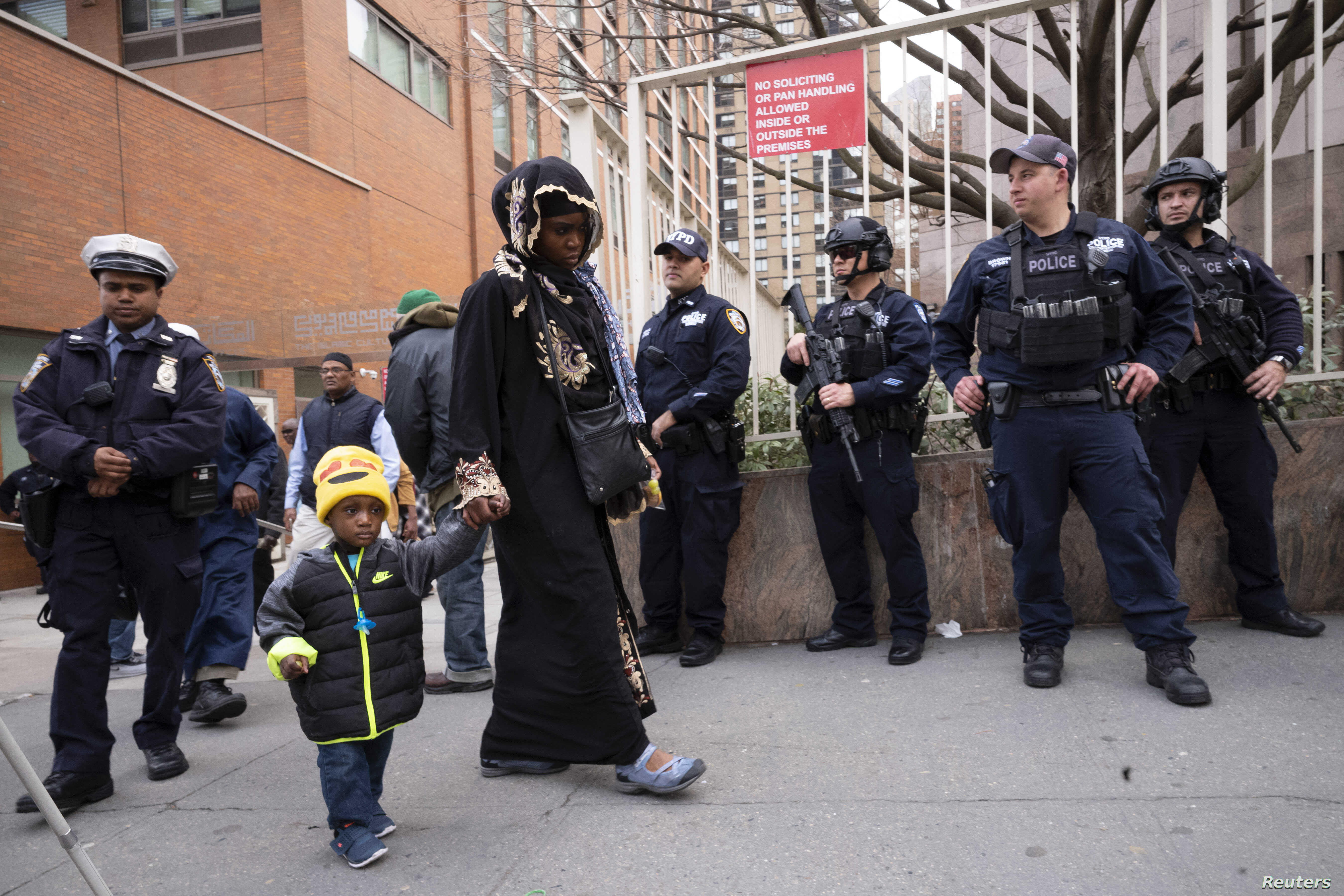 People leave the Islamic Cultural Center of New York under increased police security following the shooting in New Zealand,  March 15, 2019, in New York.