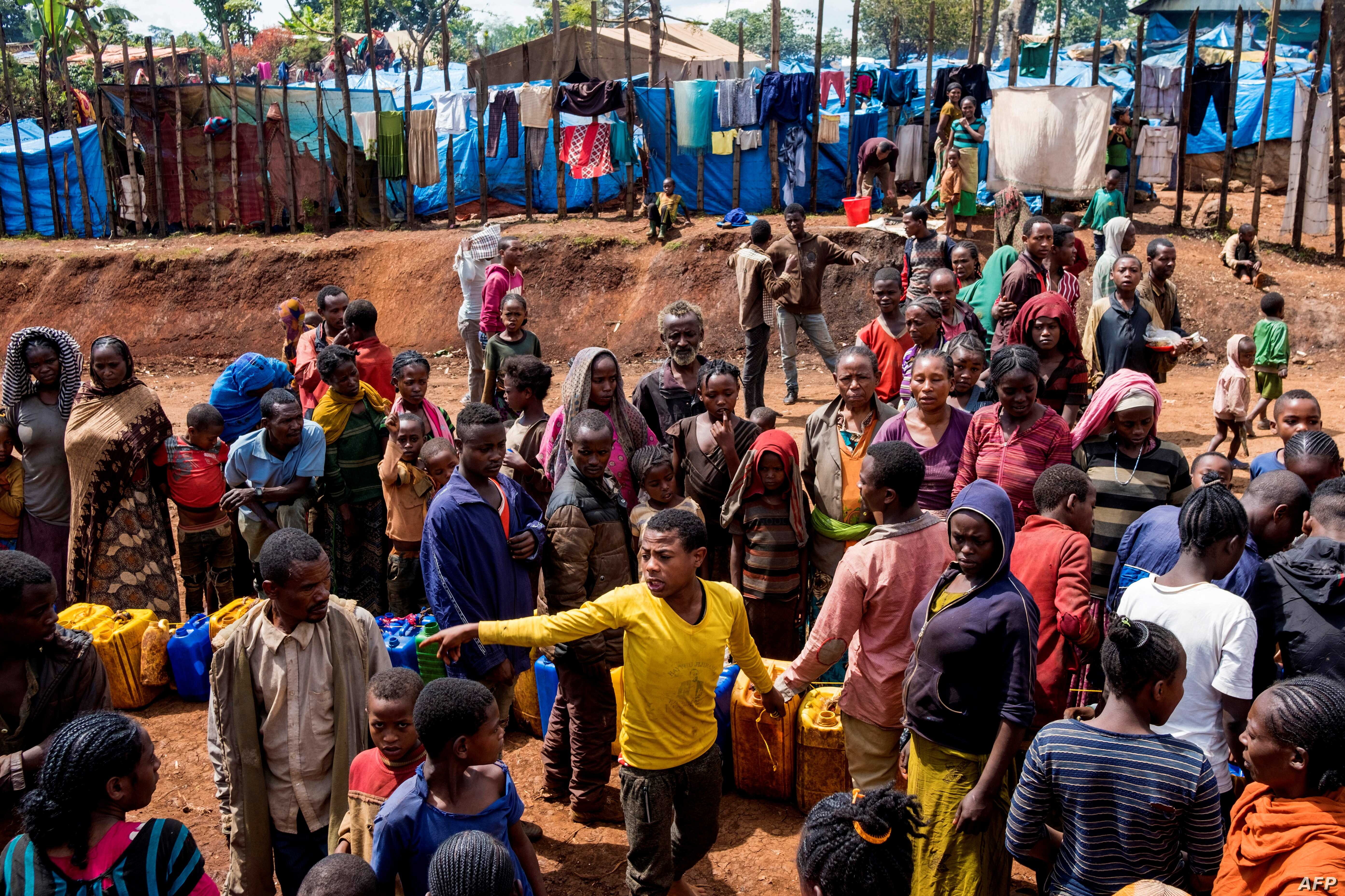 Displaced Gedeo people wait in line with their containers looking for water at Kercha site, West Guji in Ethiopia, Aug. 1, 2018. Ethiopia's Prime Minister Abiy Ahmed's aggressive reform agenda has won praise, but analysts warn that shaking up Ethiopi...