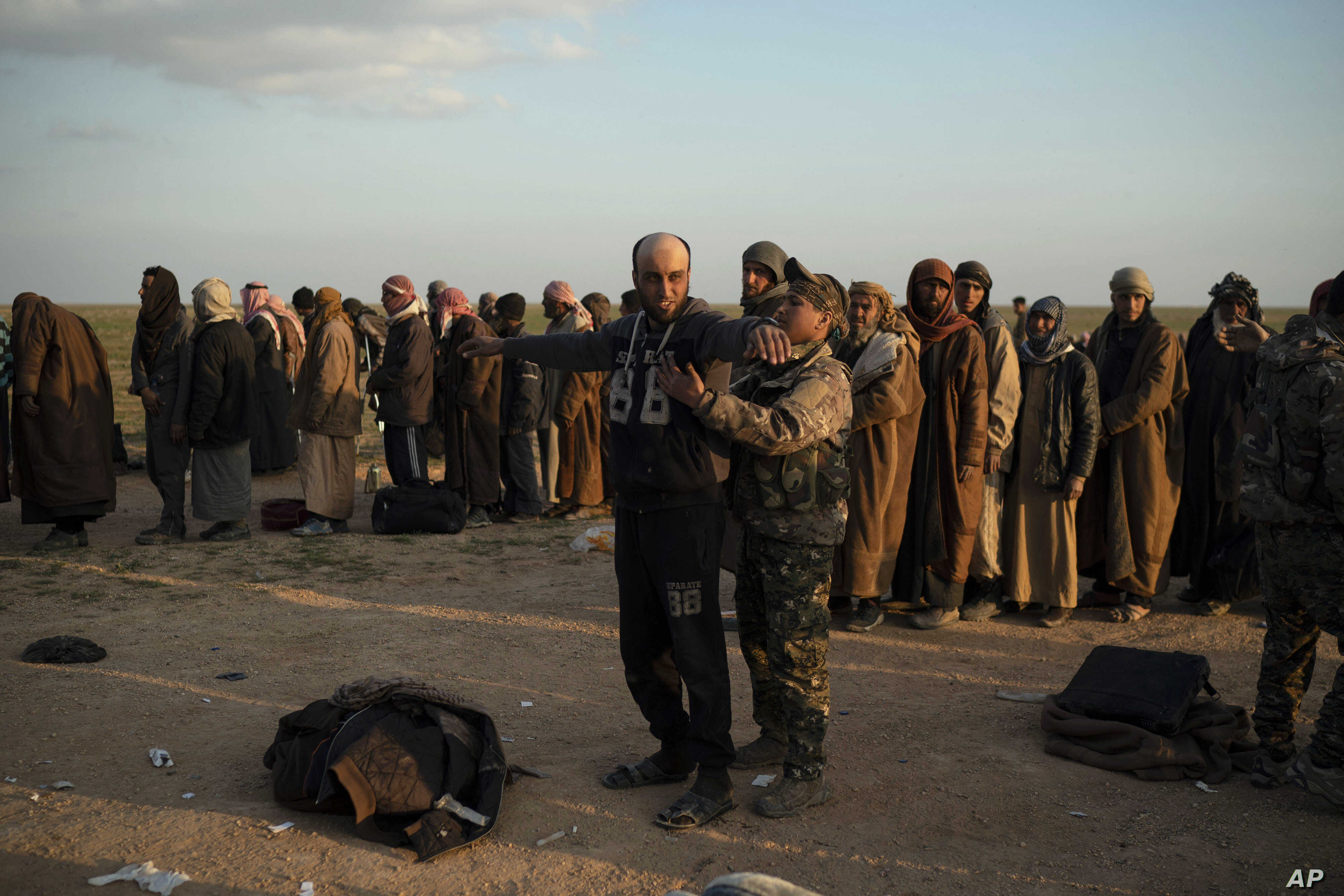 FILE - In this Feb. 22, 2019, file photo, a man is frisked by a U.S.-backed Syrian Democratic Forces fighter after being evacuated out of the last territory held by Islamic State militants, near Baghuz, eastern Syria.