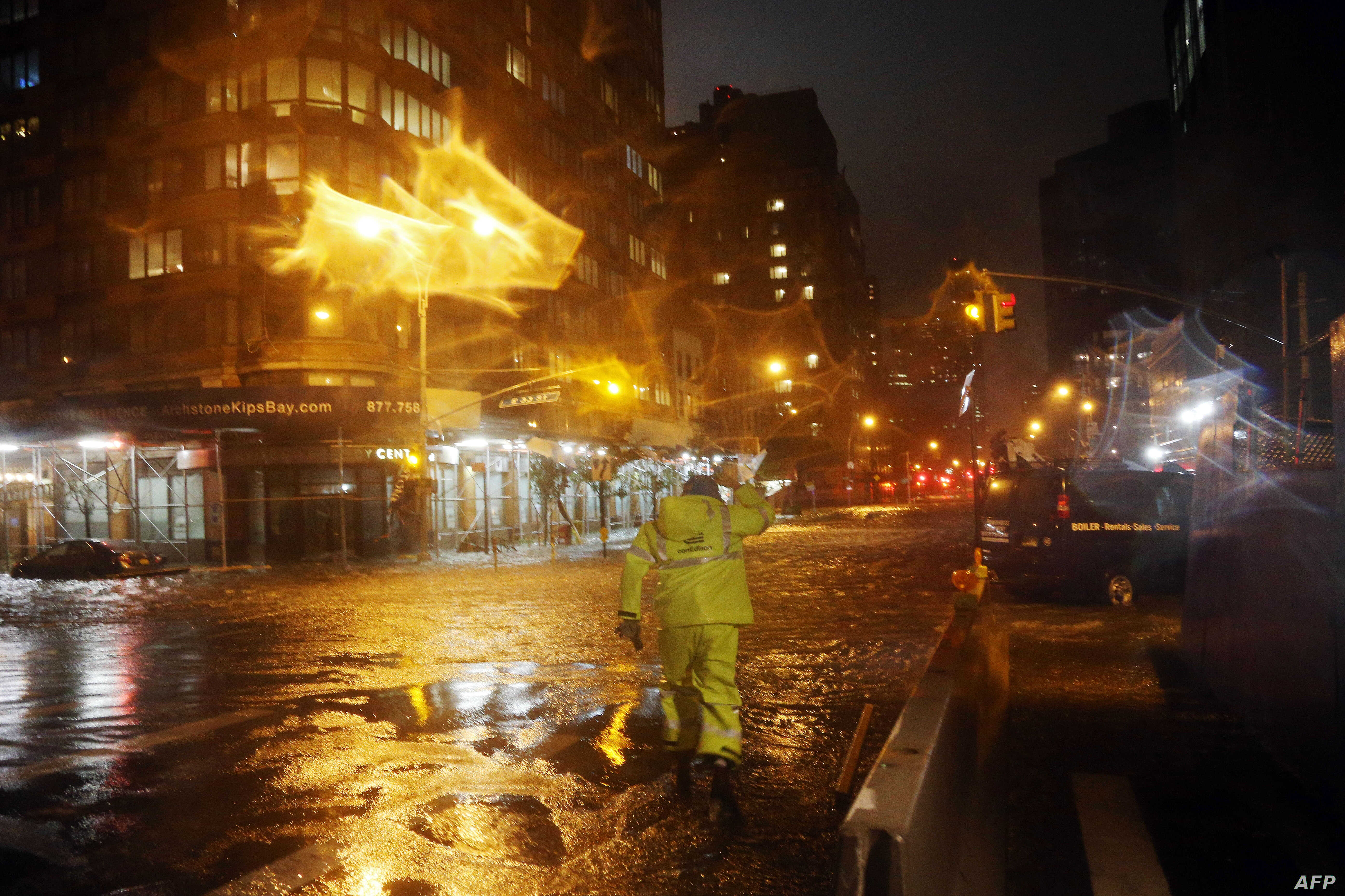 A Con Edison worker walks through the flood waters on the corner of 33th Street and 1st Street in front of NYU Langone Medical Center in Manhattan during rains from Hurricane Sandy on Oct. 29, 2012 in New York City. (Michael Heiman/Getty Images/AFP)