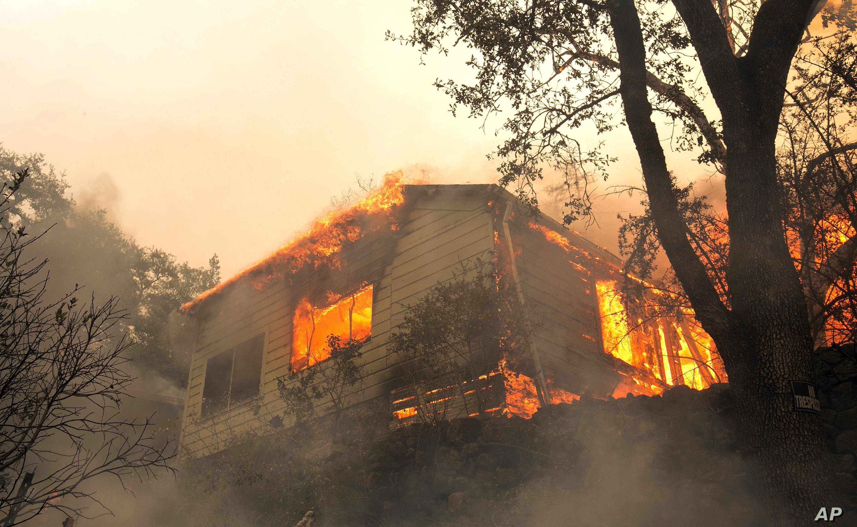 Flames from a massive wildfire consume a home on the Silverado Trail, east of Napa, Calif., Oct. 9, 2017.