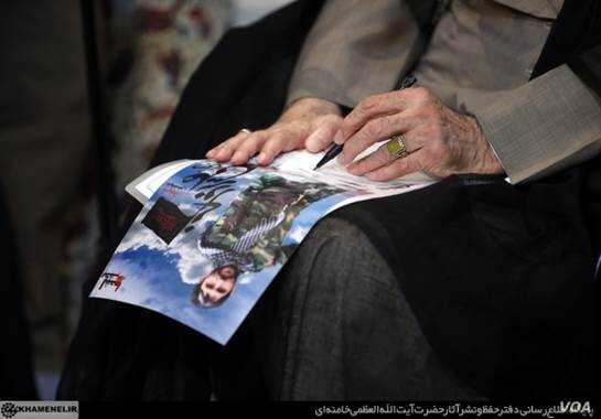 A photo shows Iran's supreme leader, Ayatollah Ali Khamenei, signing a poster of a fallen shrine defender. Source: Khamenei.ir
