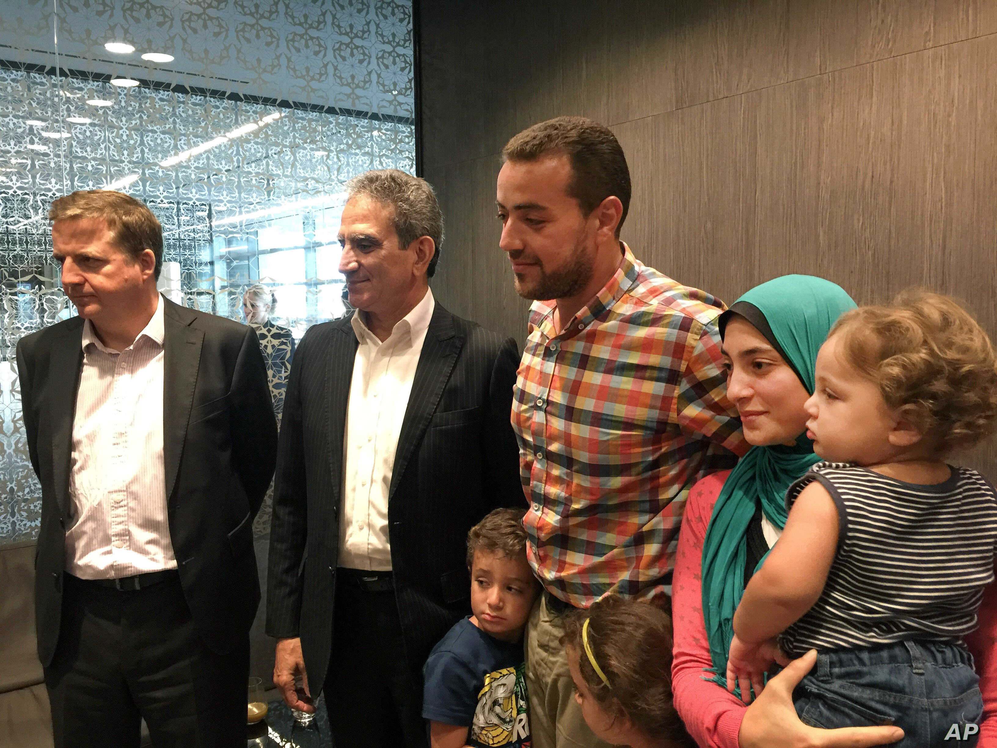 Egyptian Al-Jazeera English journalist Baher Mohammed and his family are welcomed by his colleagues in Doha, Qatar, Oct. 14, 2015.