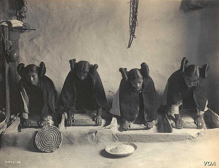This 1906 photo by Edward S. Curtis shows Hopi women grinding grain into flour.