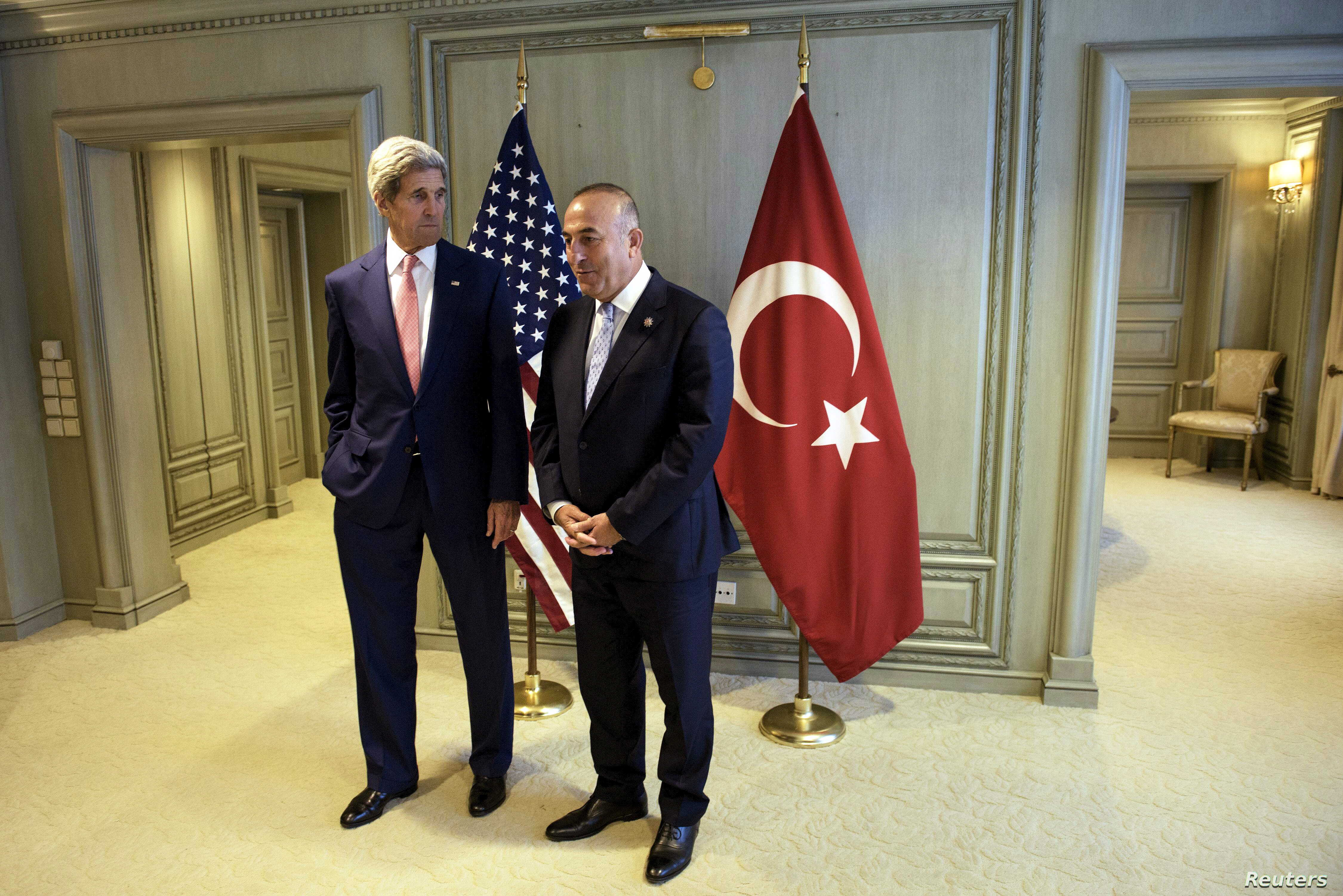U.S. Secretary of State John Kerry, left, and Turkey's Foreign Minister Mevlut Cavusoglu wait for a meeting in Kuala Lumpur, August 5, 2015.