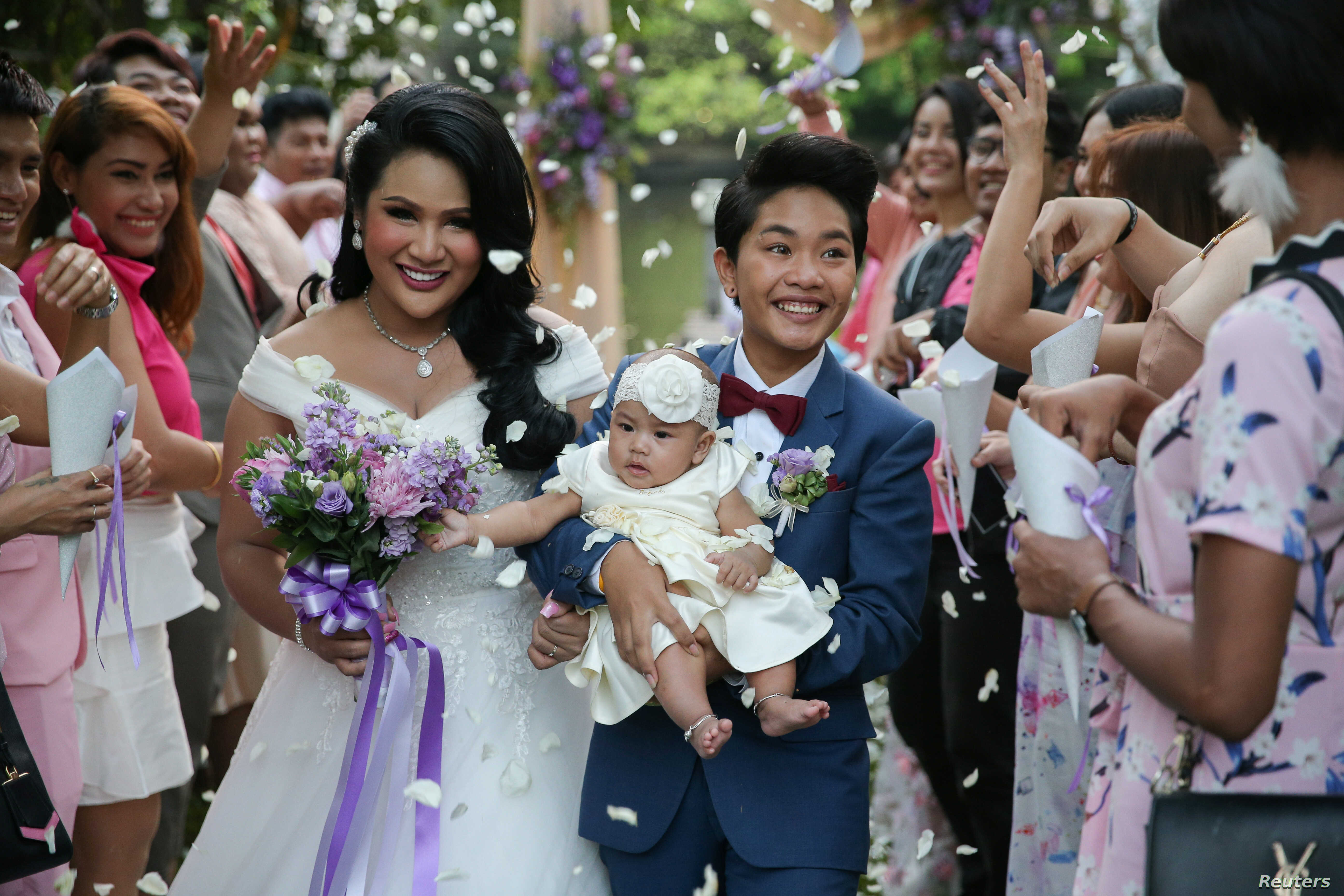 Bride Amornrat Ruamsin (L), 27, who is a transgender, holds up her five-month-old daughter with her groom Pitchaya Kachainrum (R), 16, during their wedding ceremony organised by a local TV show, in Bangkok, Thailand, February 9, 2018.