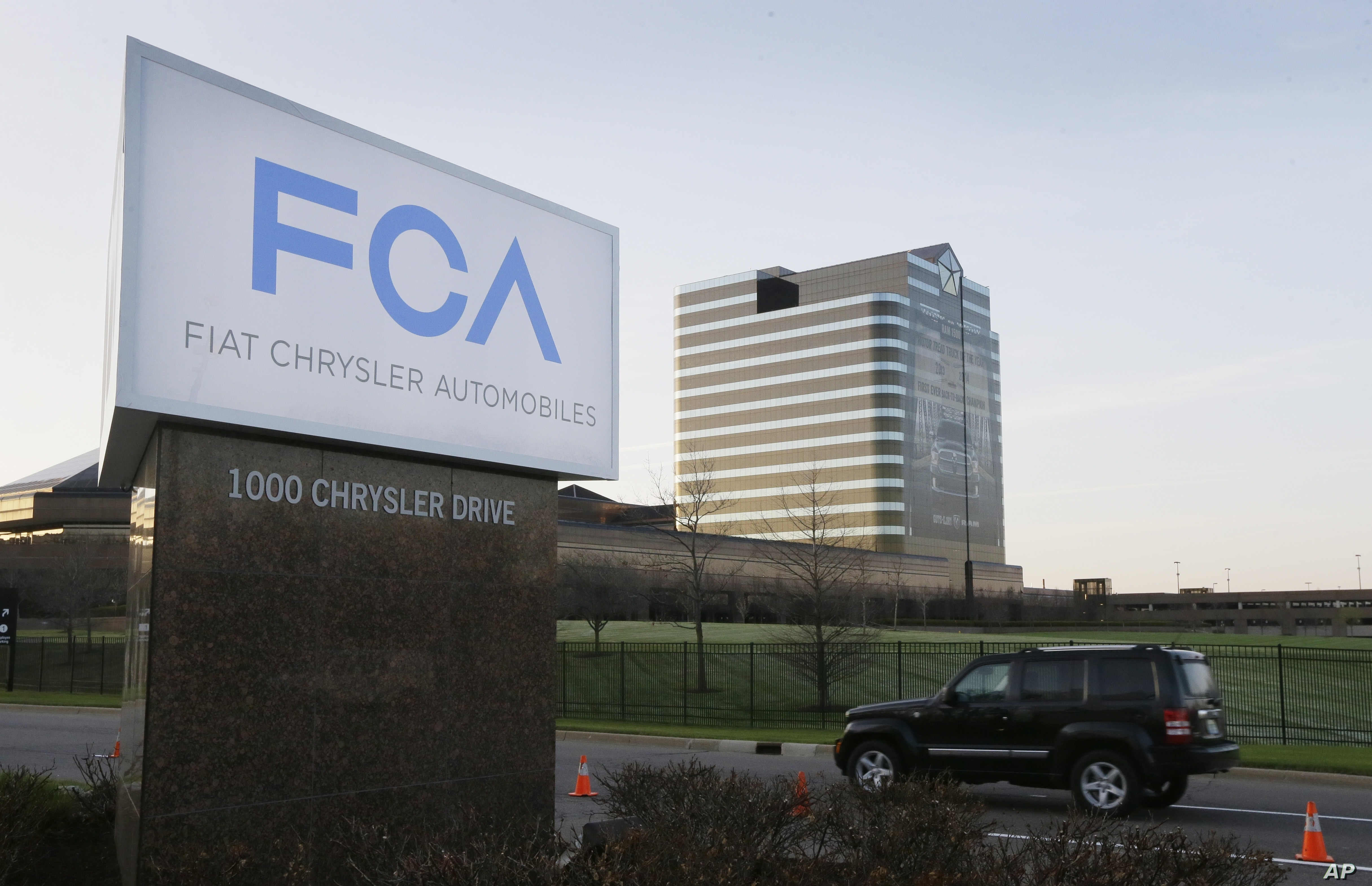 FILE - In this May 6, 2014, photo, a vehicle moves past a sign outside Fiat Chrysler Automobiles world headquarters in Auburn Hills, Michigan.