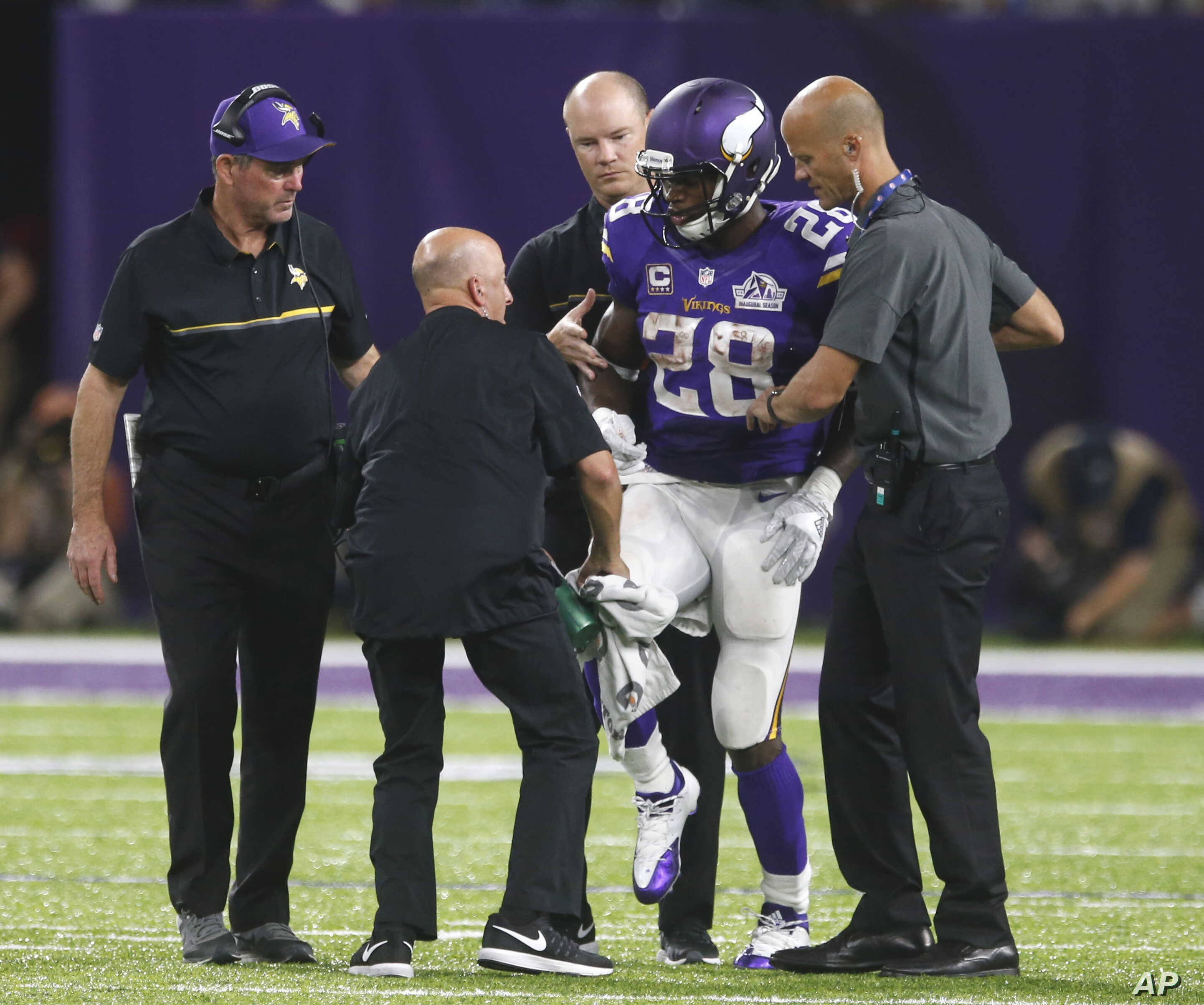 Minnesota Vikings running back Adrian Peterson (28) is helped off the field after getting injured during an NFL football game against the Green Bay Packers, Sept. 18, 2016.