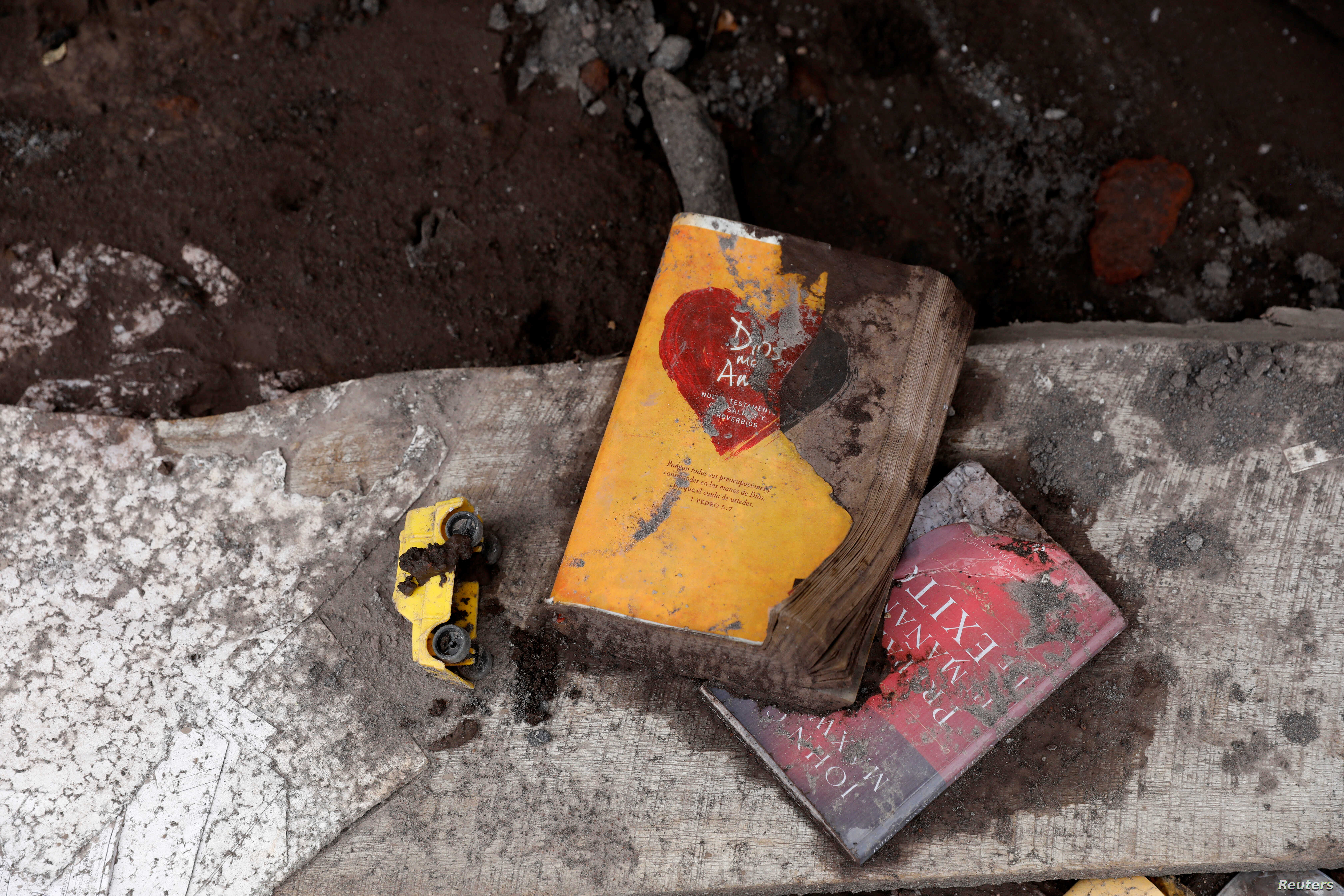 Books and a toy lie on the ground at a house affected by the eruption of the Fuego volcano in San Miguel Los Lotes in Escuintla, Guatemala, June 8, 2018.