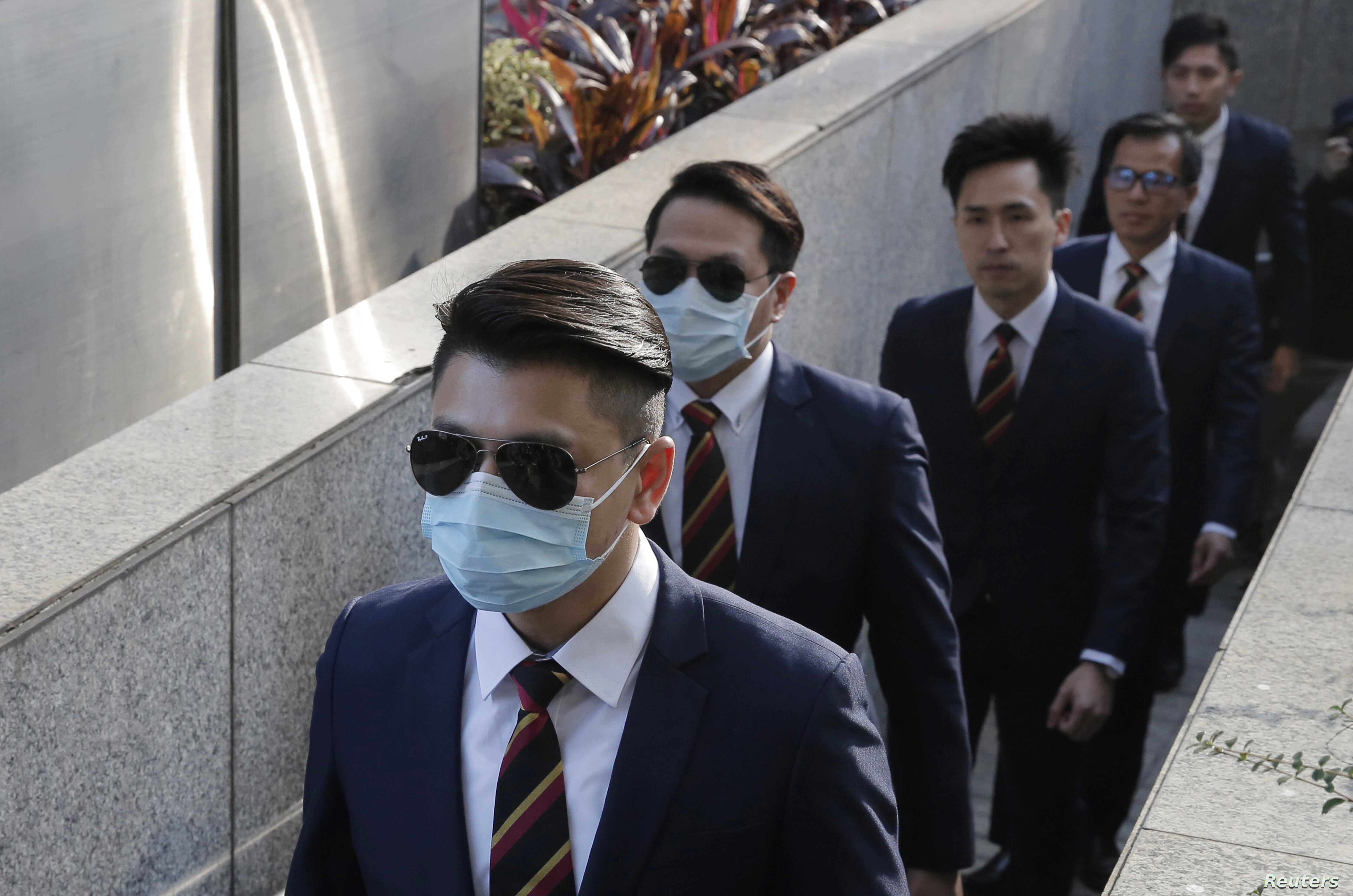 FILE - In this Feb. 14, 2017 file photo, five of the seven Hong Kong police officers arrive the District Court in Hong Kong as they were charged with assaulting a pro-democracy activist in an incident on Oct. 15 2014.