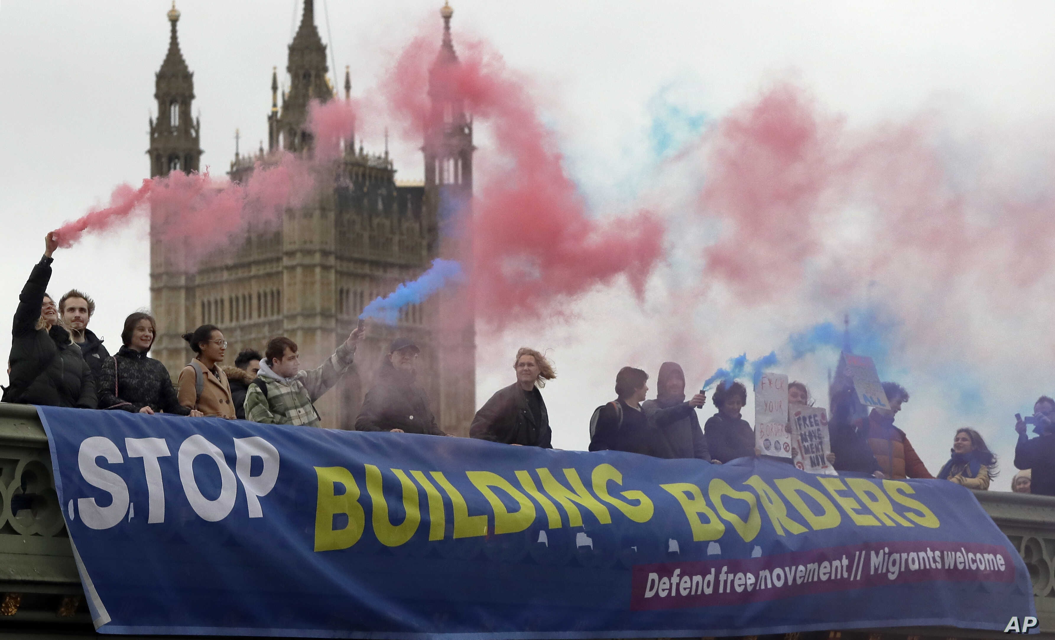 Demonstrators hold flares and a banner over Westminster Bridge in front of the Parliament buildings in London, Nov. 28, 2018. Campaigners from Another Europe is Possible and the Labor Campaign for Free Movement took part in a stunt and flash protest ...