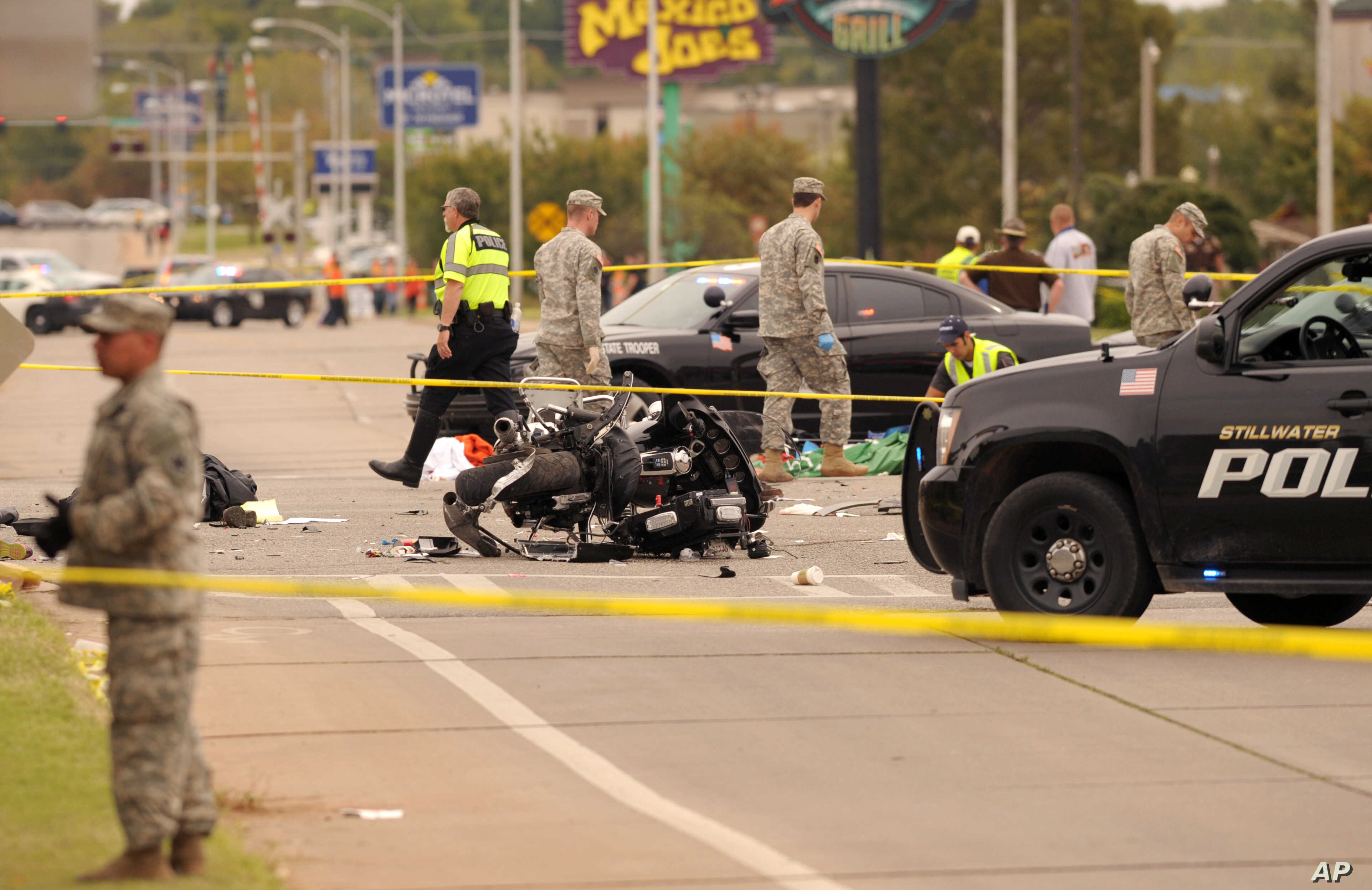 A damaged police motorcycle rests in the intersection after a vehicle crashed into a crowd of spectators during the Oklahoma State University homecoming parade, causing multiple injuries and deaths, in Stillwater, Okla., Oct. 24, 2015.