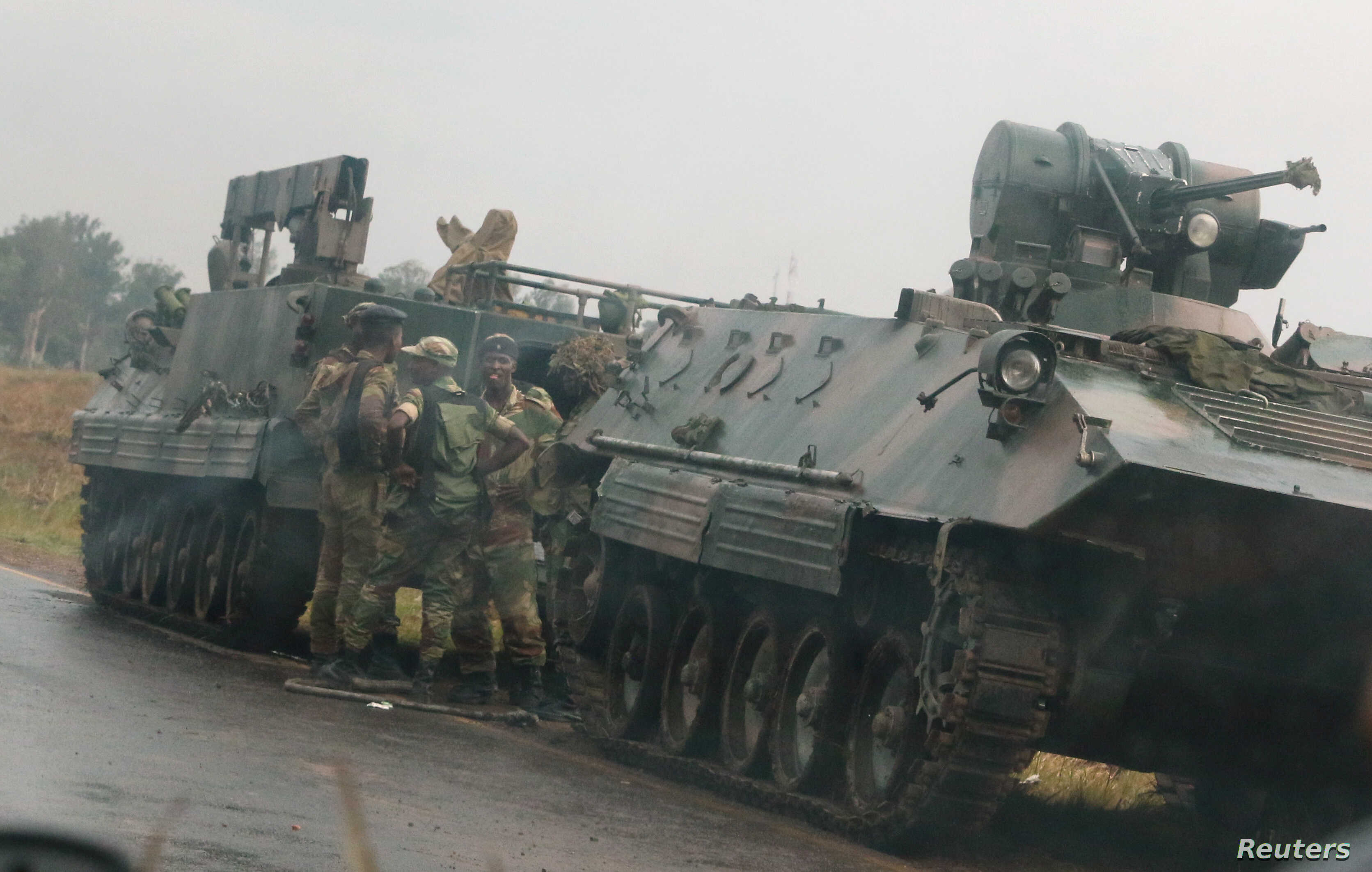 Soldiers stand beside military vehicles just outside Harare, Zimbabwe, Nov. 14,2017.