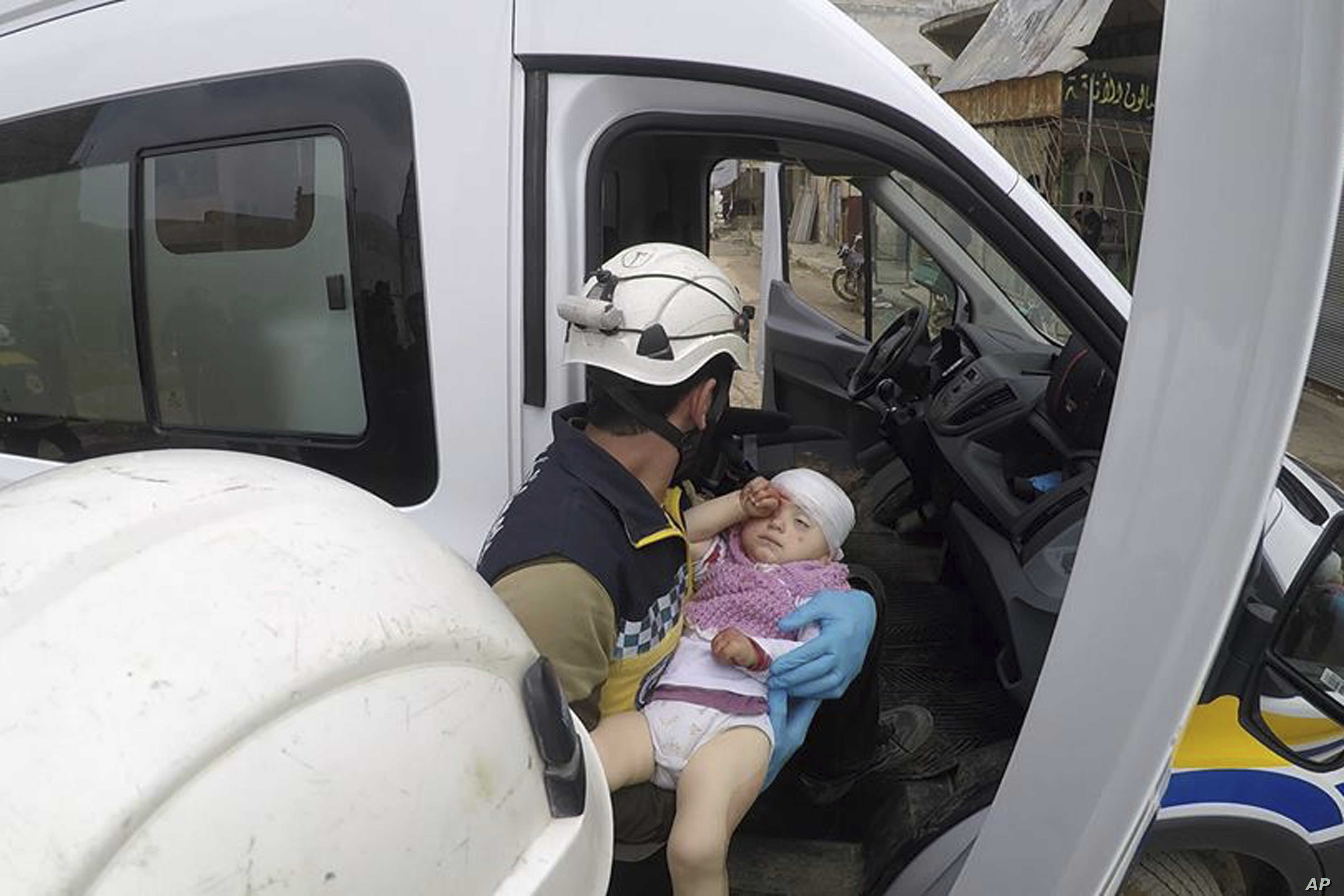 This photo provided by the Syrian Defense White Helmets shows a civil defense worker carrying a child after shelling hit a street in the town of Nairab, in the eastern province of Idlib, Syria,  Apr. 7, 2019.