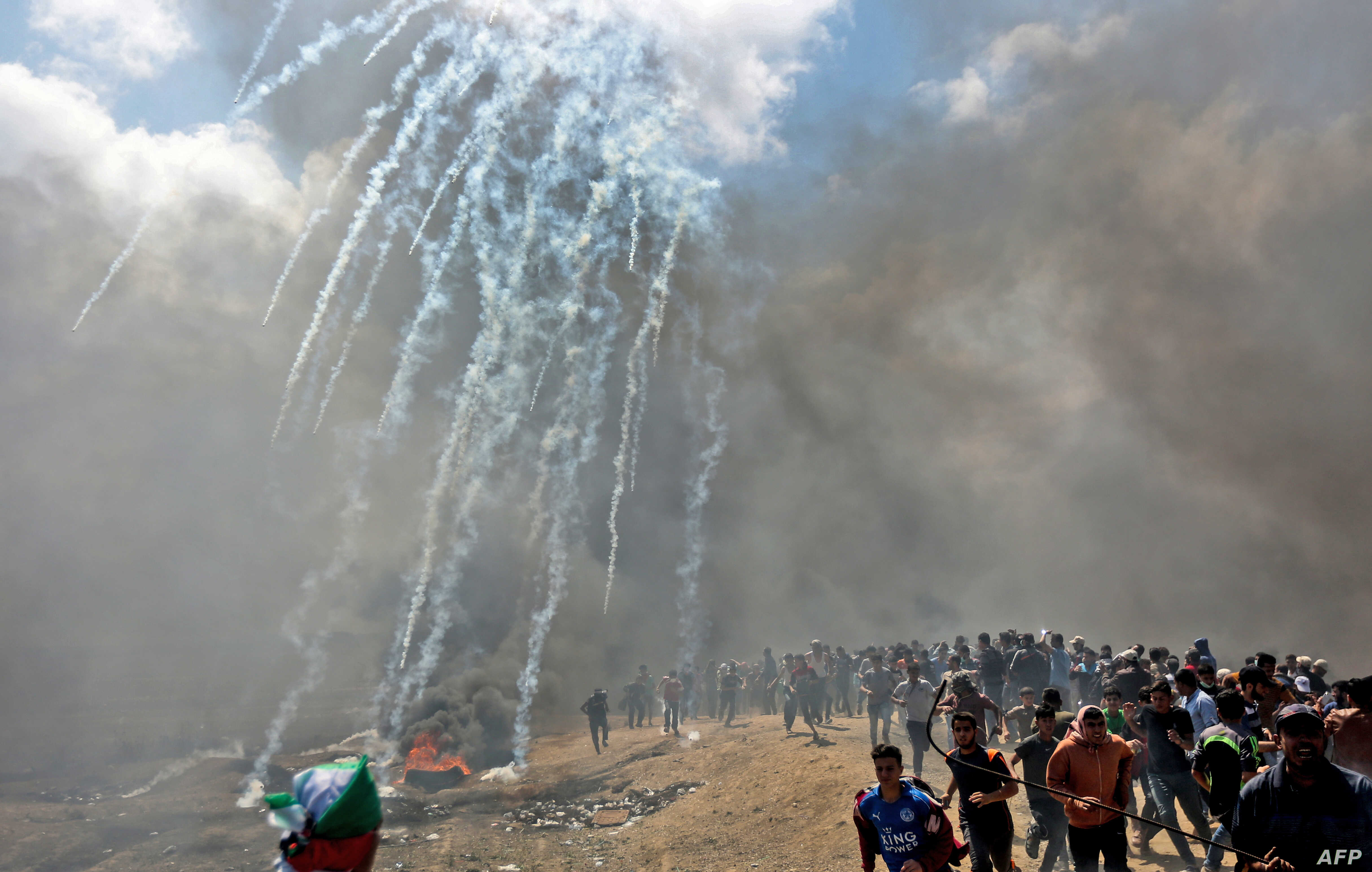 Palestinians run for cover from tear gas fired by Israeli forces near the border between the Gaza strip and Israel east of Gaza City, May 14, 2018, as Palestinians protest over the inauguration of the US embassy following its controversial move to Je...