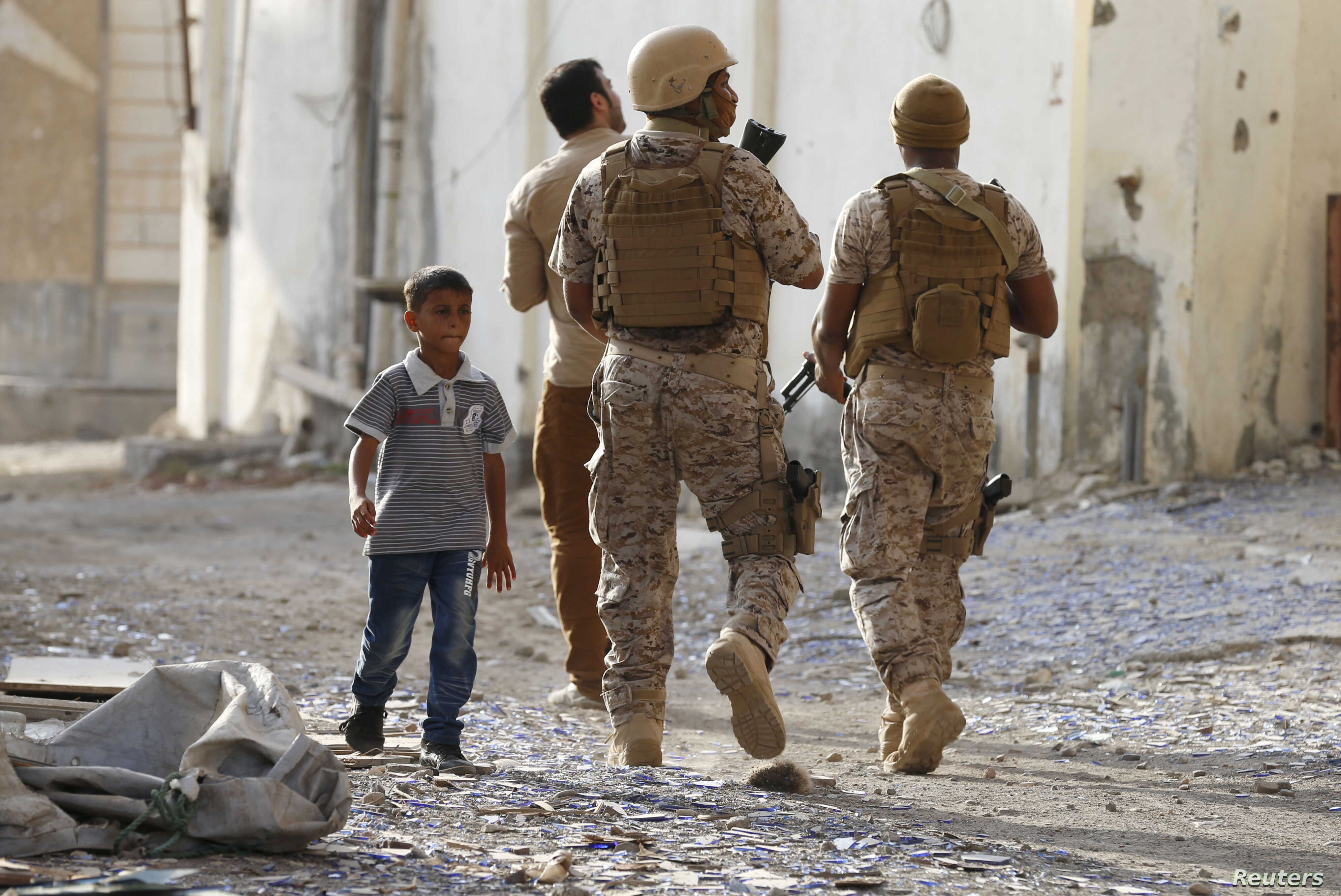 FILE - A boy walks past soldiers from the Saudi-led coalition patrolling a street in Yemen's southern port city of Aden, Sept. 26, 2015.