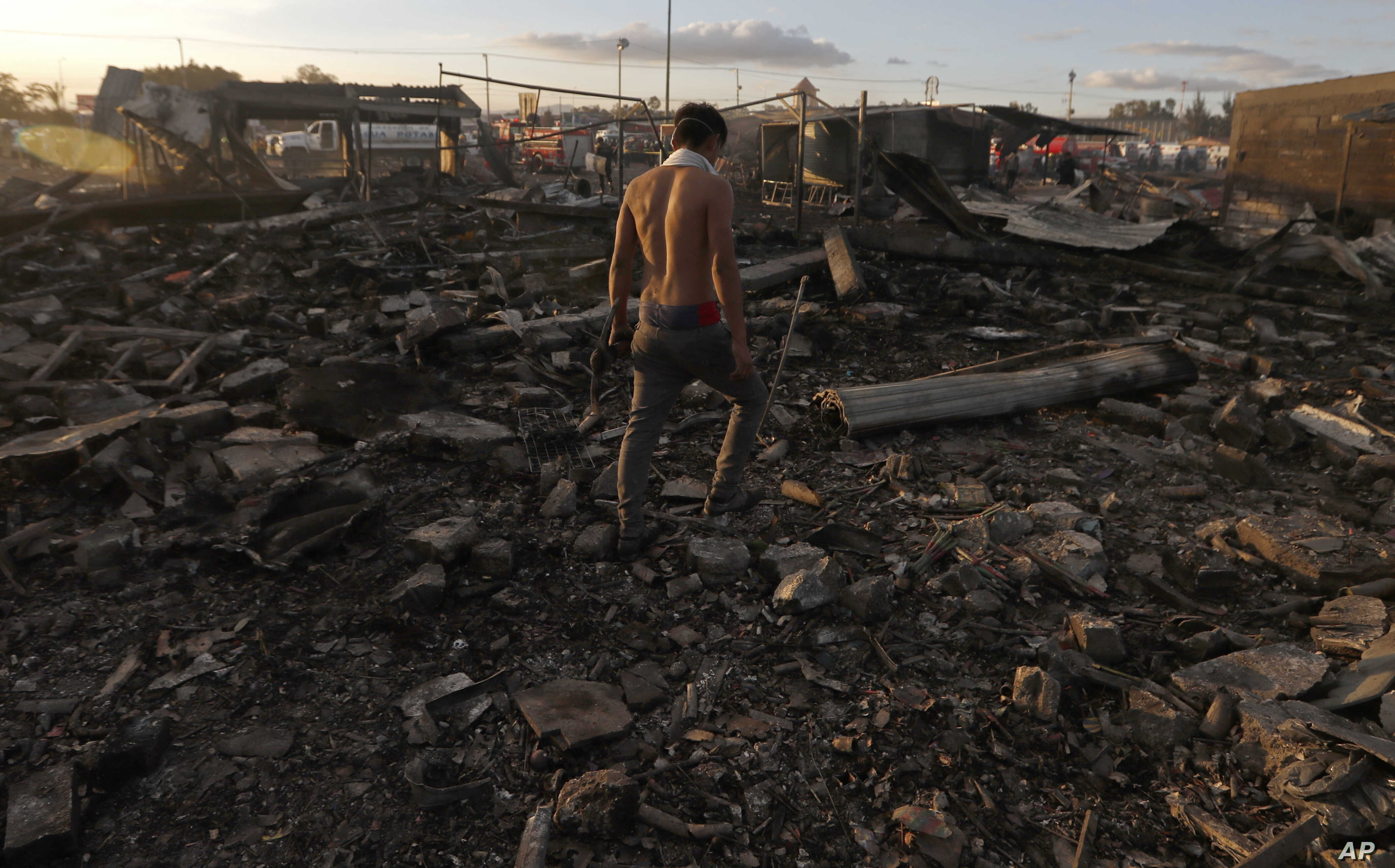 A man walks  through the scorched ground of the open-air San Pablito fireworks market, in Tultepec, outskirts of Mexico City, Mexico, Dec. 20, 2016.  An explosion ripped through Mexico's best-known fireworks market where most of the fireworks stal...