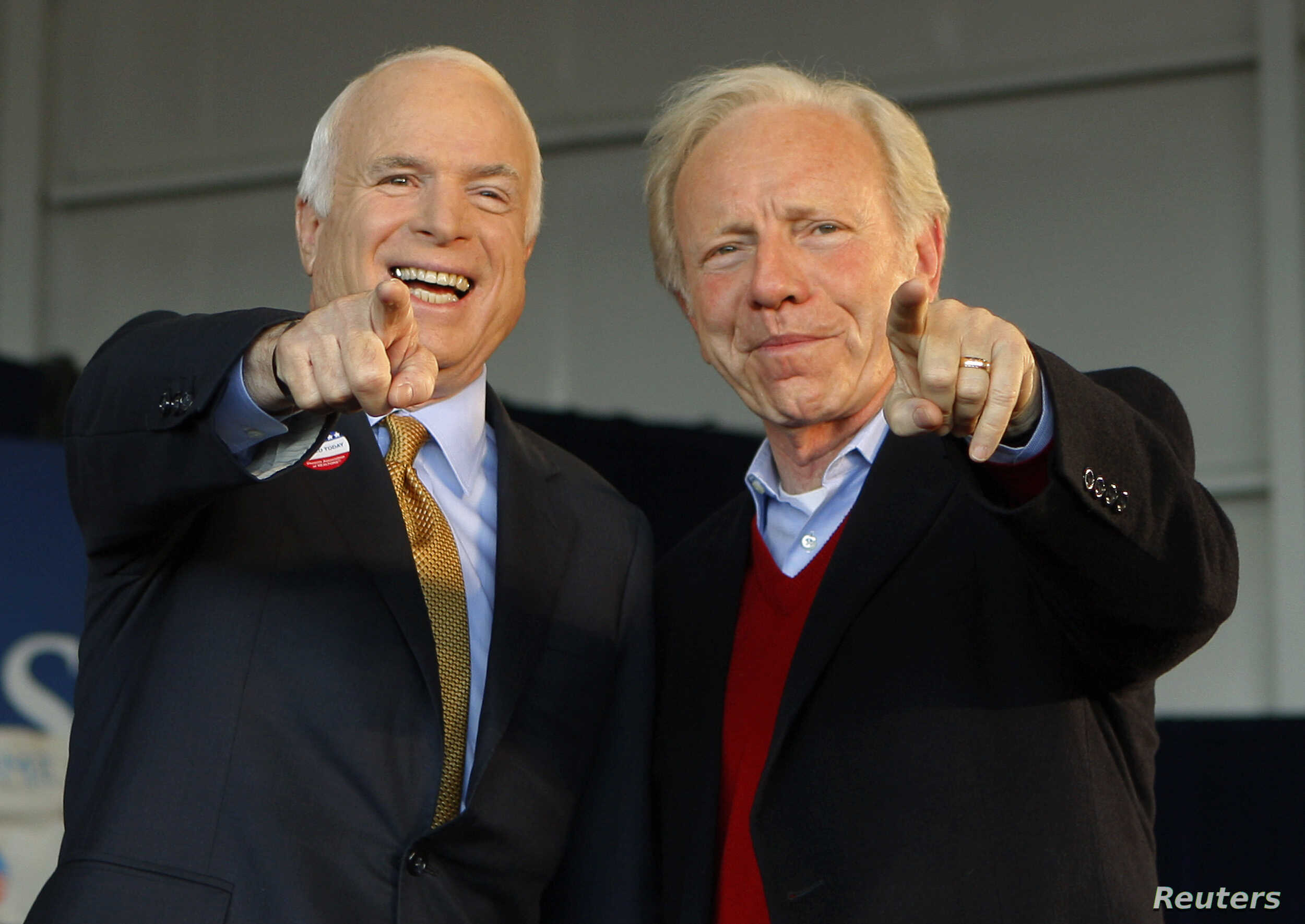 U.S. Republican presidential nominee Senator John McCain (R-AZ) (L) and U.S. Senator Joe Lieberman (I-CT) point to a sign in the crowd at a campaign rally in Grand Junction, Colorado November 4, 2008, the day of the U.S. presidential election.