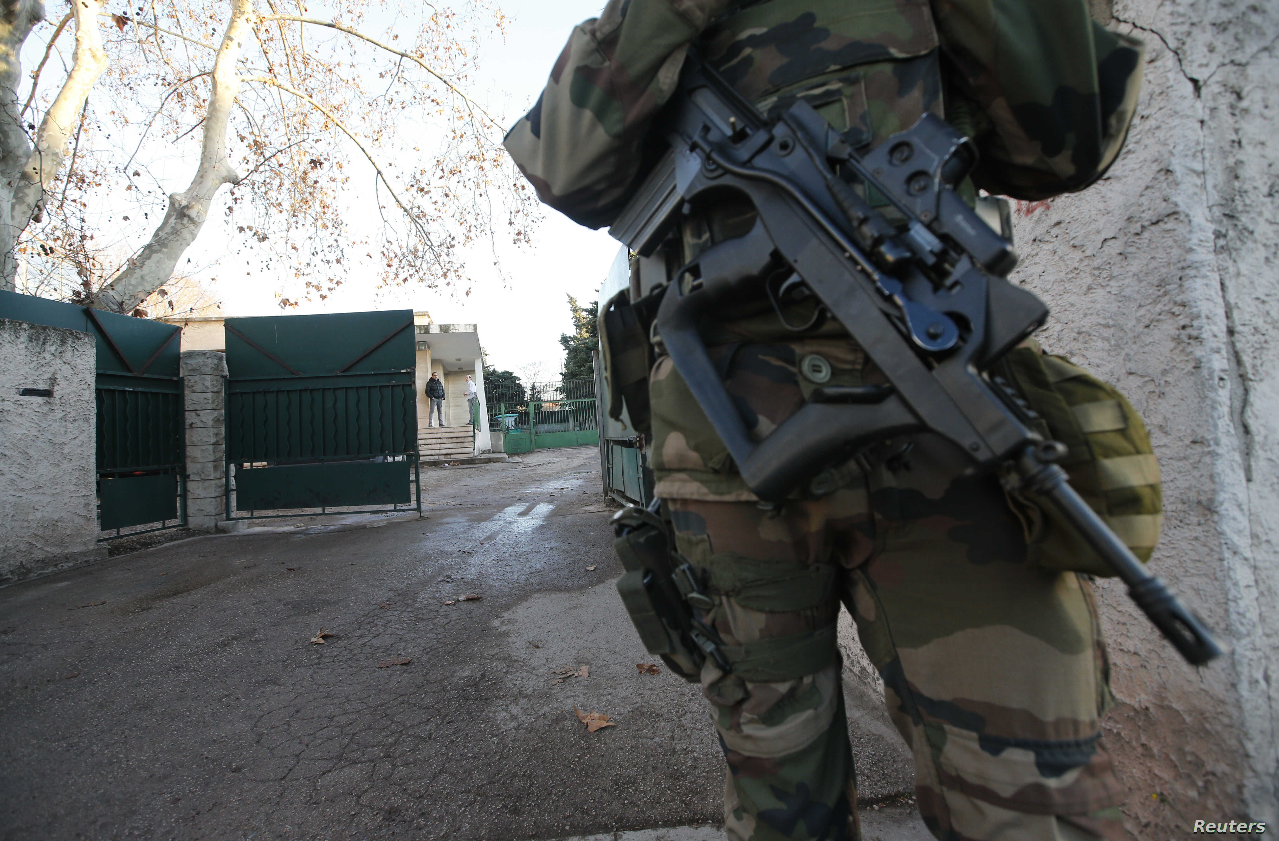 An armed French soldier secures the access to a Jewish school in Marseille's 9th district, France, Jan, 11, 2016, after a teenager, armed with a machete and a knife, wounded a teacher slightly before being stopped and arrested.