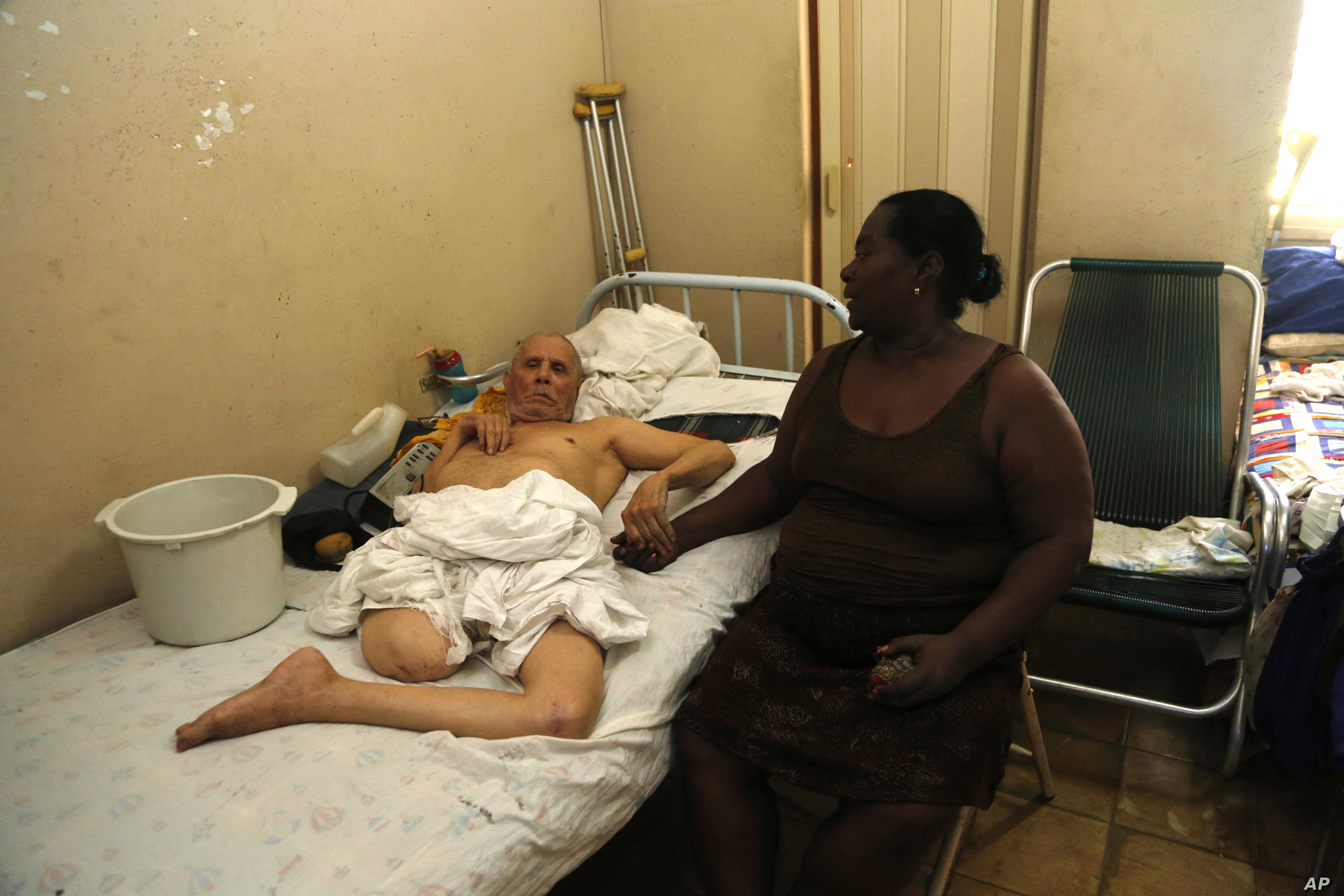 In this Aug. 24, 2015, photo, Bertha More, 54, sits with her husband Alberto Espinosa, 79, a former restaurant worker who was paralyzed by a stroke seven years ago and later lost a leg to circulation problems, in Havana, Cuba.