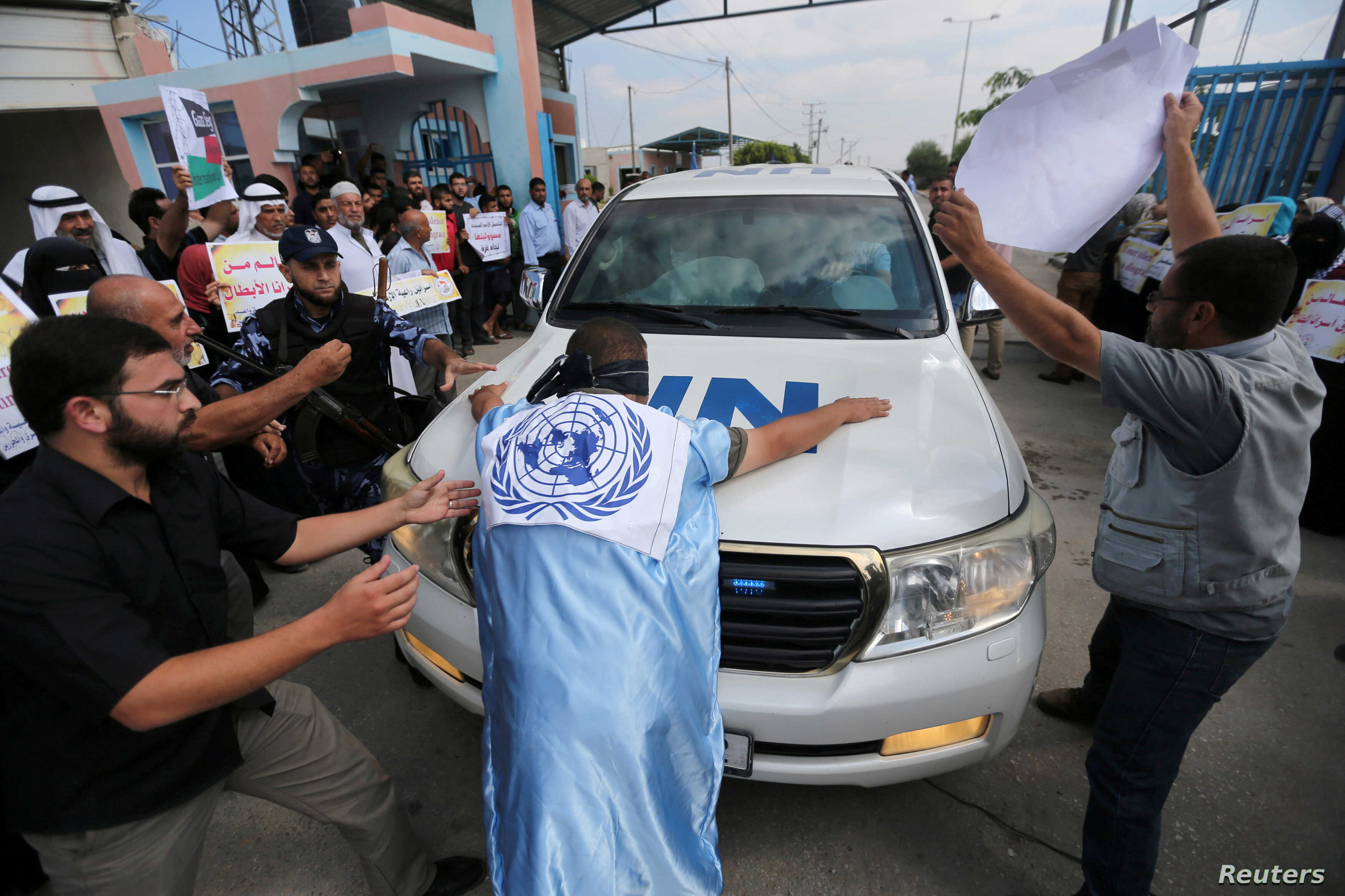 Palestinians try to block the convoy of United Nations Secretary-General Antonio Guterres upon his arrival near Erez crossing in the northern Gaza Strip, August 30, 2017.