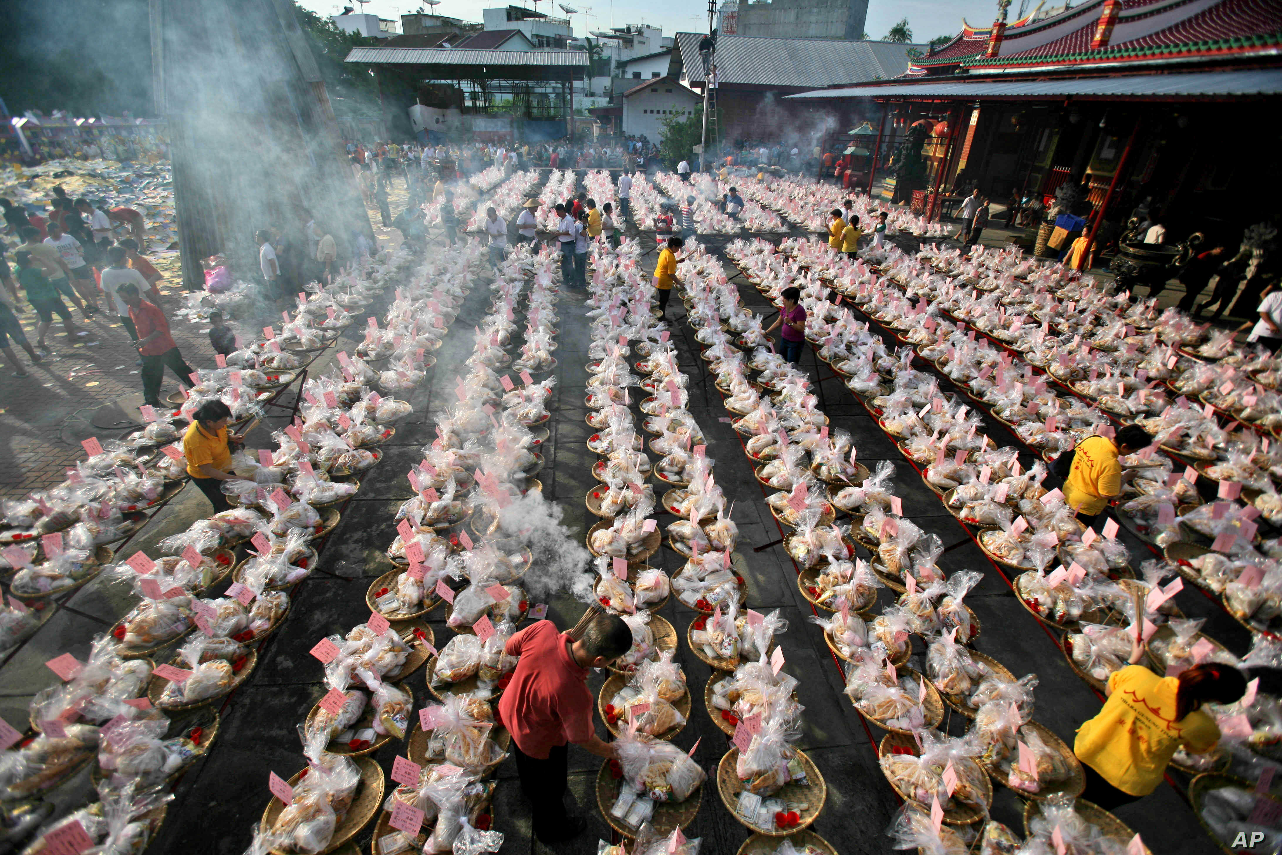 """Ethnic-Chinese Indonesians arrange offerings for their ancestors' souls during the """"hungry ghost"""" festival in Medan, North Sumatra, Indonesia, Sunday, Aug. 10, 2014."""