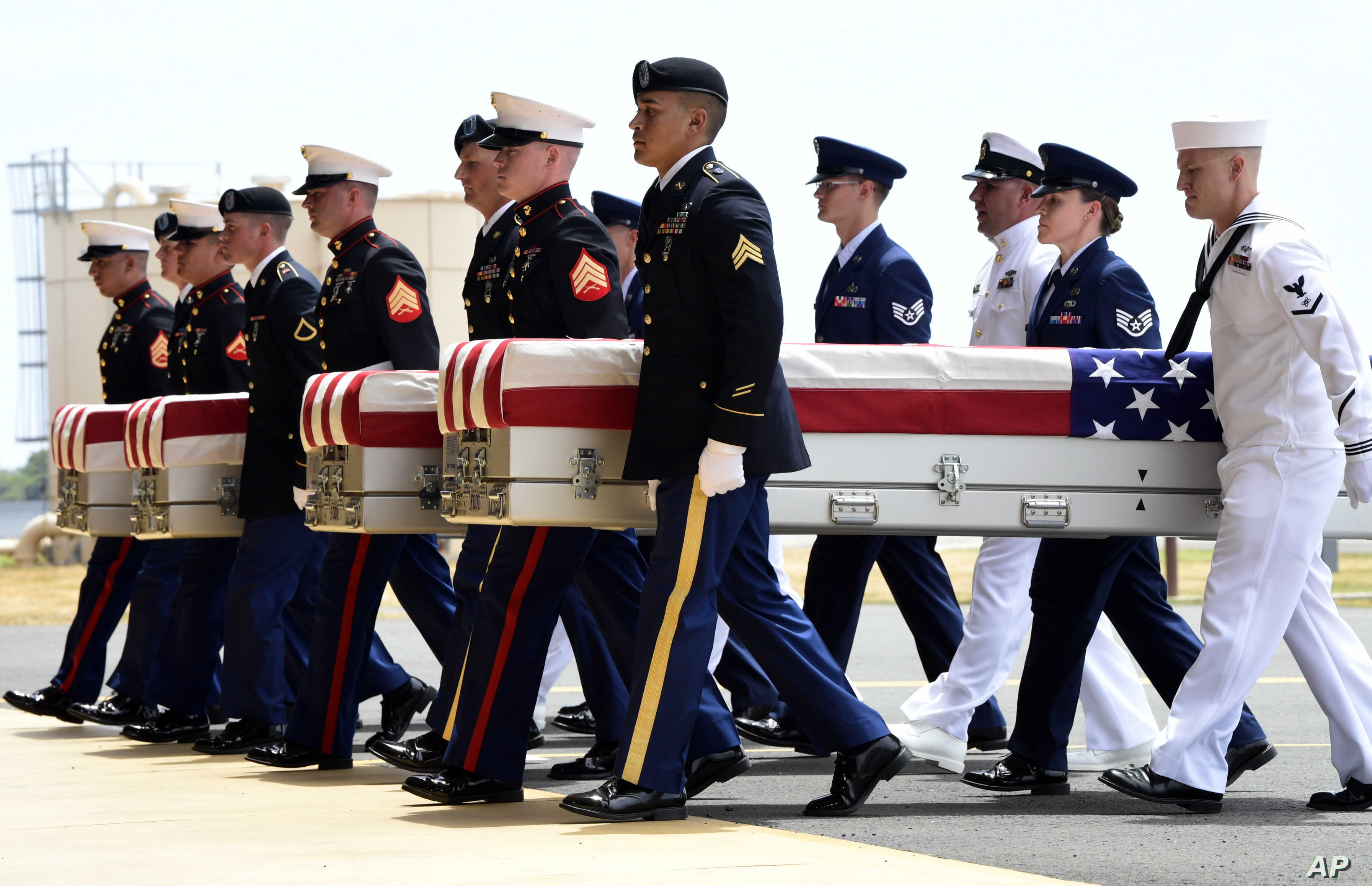 Military members carry transfer cases from a C-17 at a ceremony marking the arrival of the remains believed to be of American service members who fell in the Korean War at Joint Base Pearl Harbor-Hickam in Hawaii, Aug. 1, 2018. North Korea handed ove...