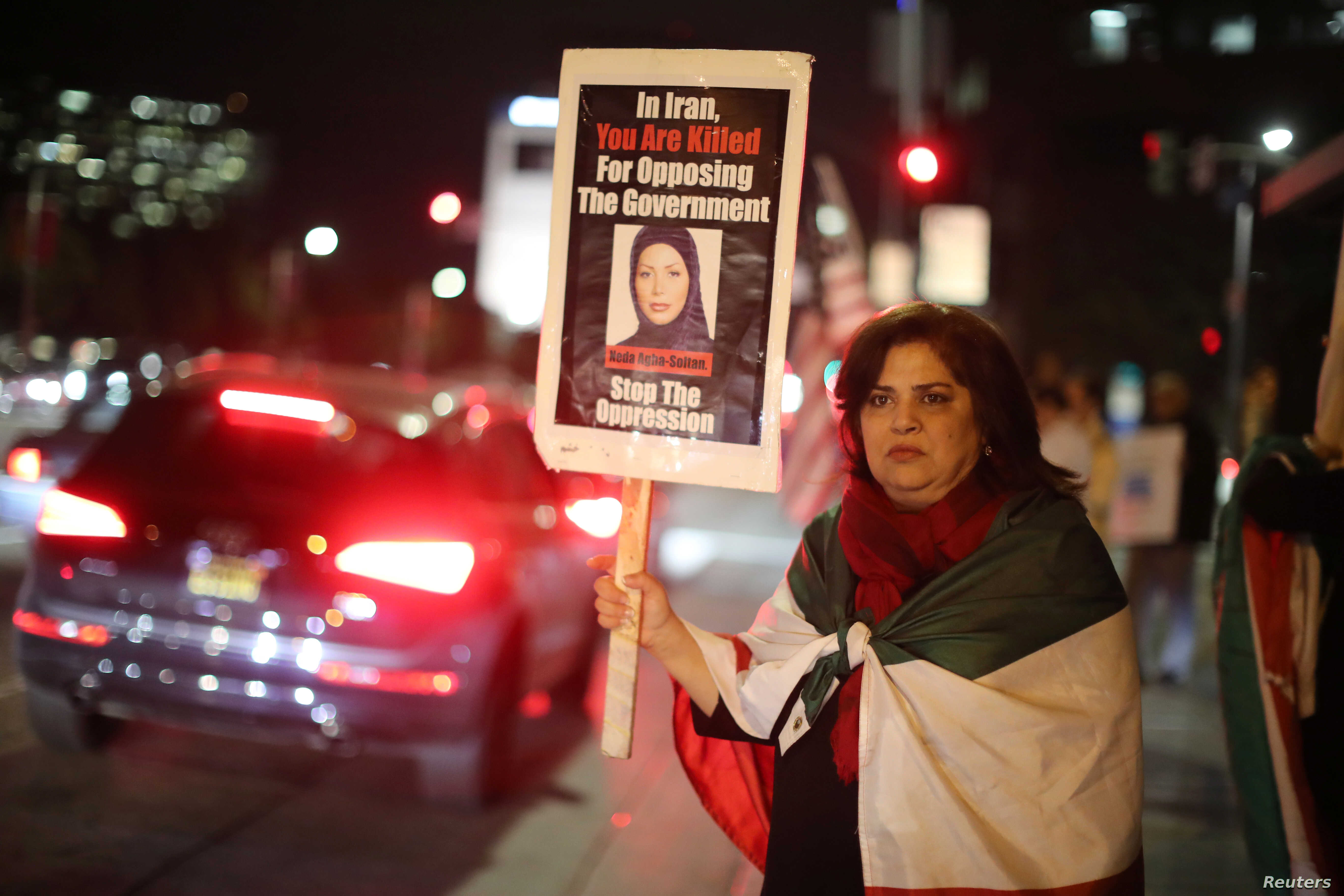 Iranian expatriate Roxanne Ganji holds a sign at a protest in Los Angeles, Jan. 3, 2018.