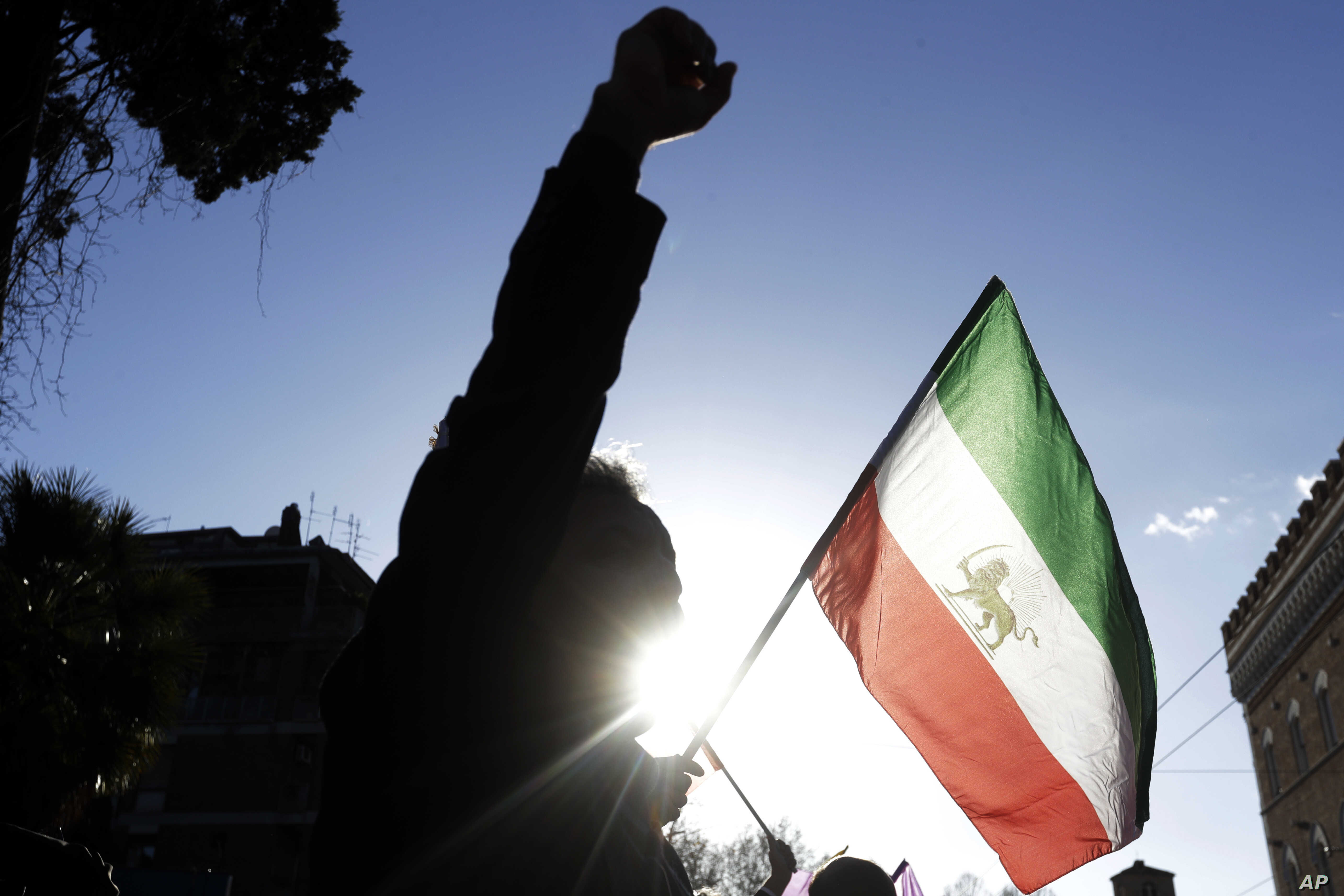 A demonstrator shouts slogans near the flag of the former Imperial State of Iran as he gathers with supporters of Maryam Rajavi, head of the Iranian opposition group National Council of Resistance, outside the Iran Embassy, in Rome, Jan. 2, 2017.