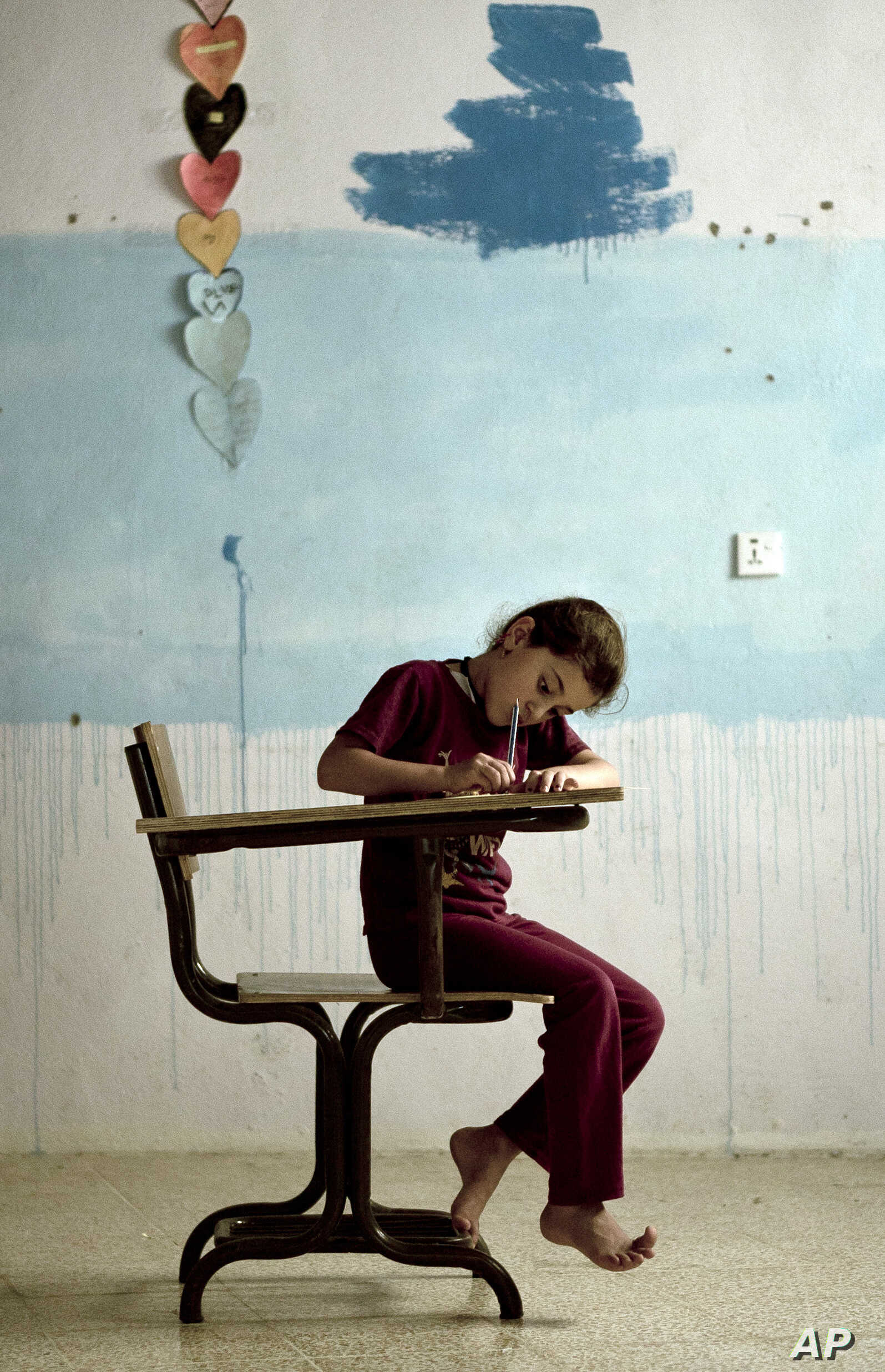In this Aug. 22, 2018 photo, an orphaned Yazidi girl draws during arts and crafts time at an orphanage in Sheikhan, Iraq.