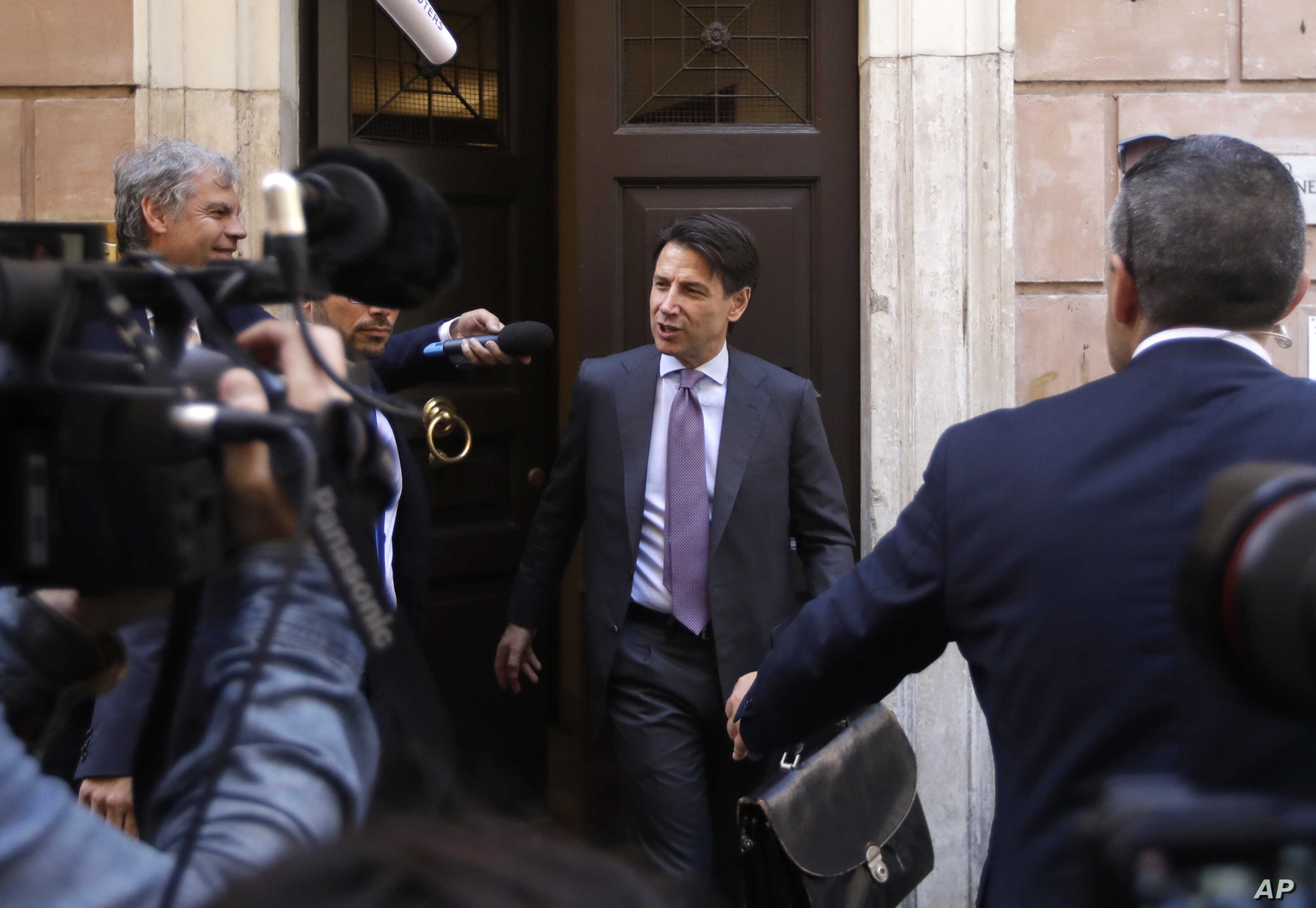 Italian Premier-designate Giuseppe Conte (C) is approached by journalists as he leaves his home, in Rome, May 24, 2018.