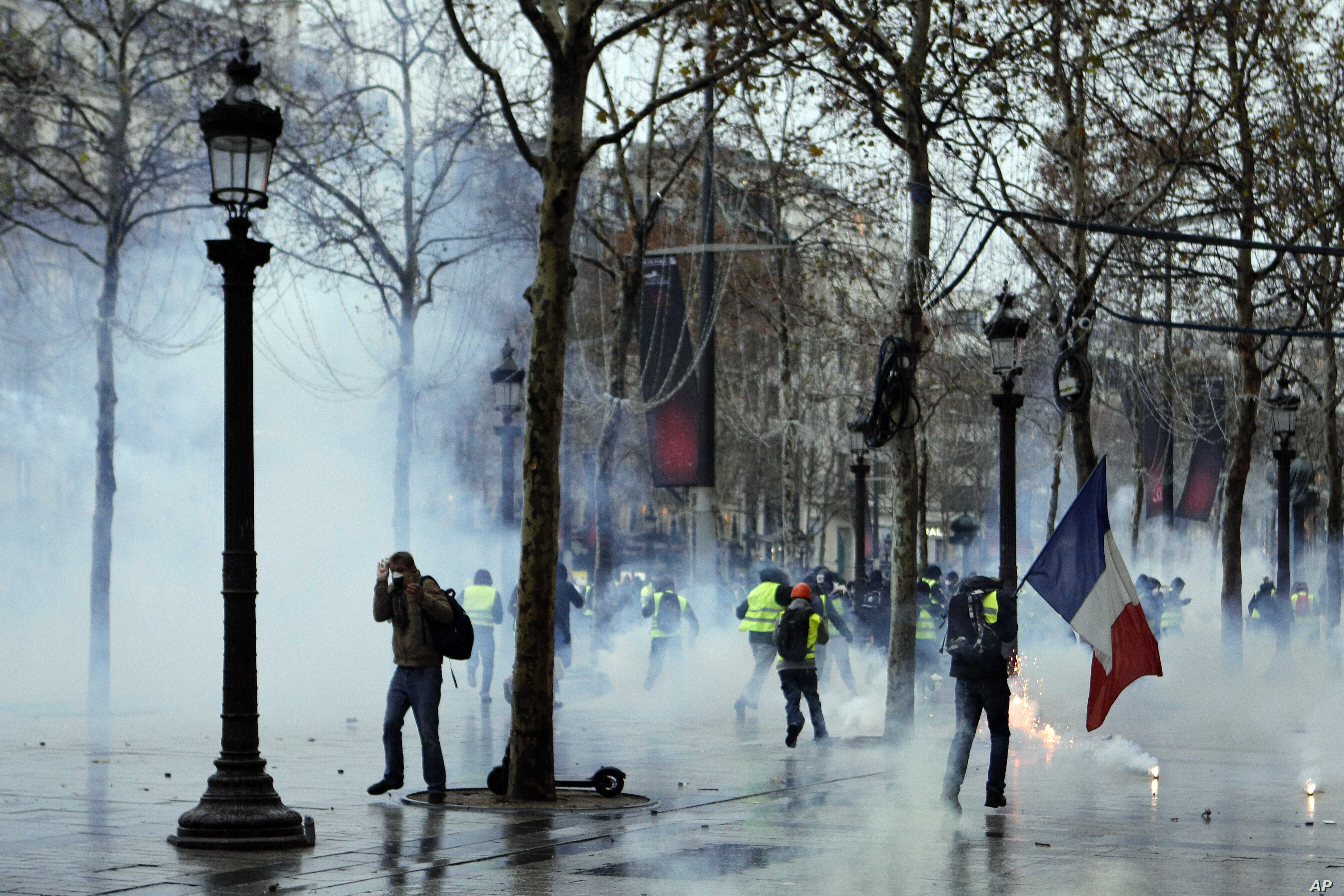"""Demonstrators run away through tear gas during scuffles on the Champs-Elysees, Dec. 15, 2018, in Paris. Protests throughout the day against France's high cost of living by """"yellow vest"""" demonstrators were largely peaceful."""