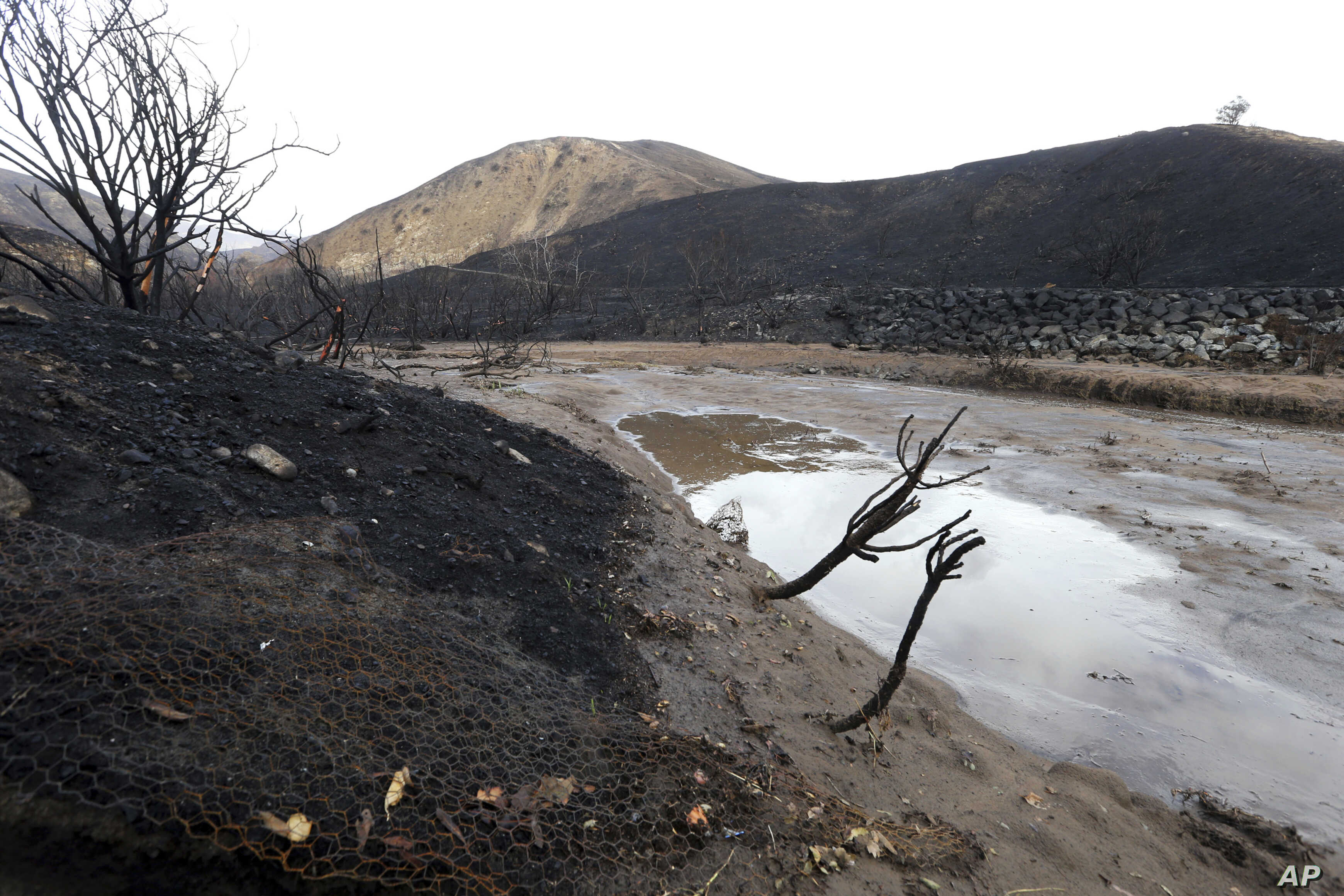 Mud and debris has washed down normally-dry Solstice Creek in an area burned by the Woolsey Fire in Malibu, Calif.,  Nov. 29, 2018. Bands of heavy rain are moving across Southern California, raising concerns about possible mudslides.