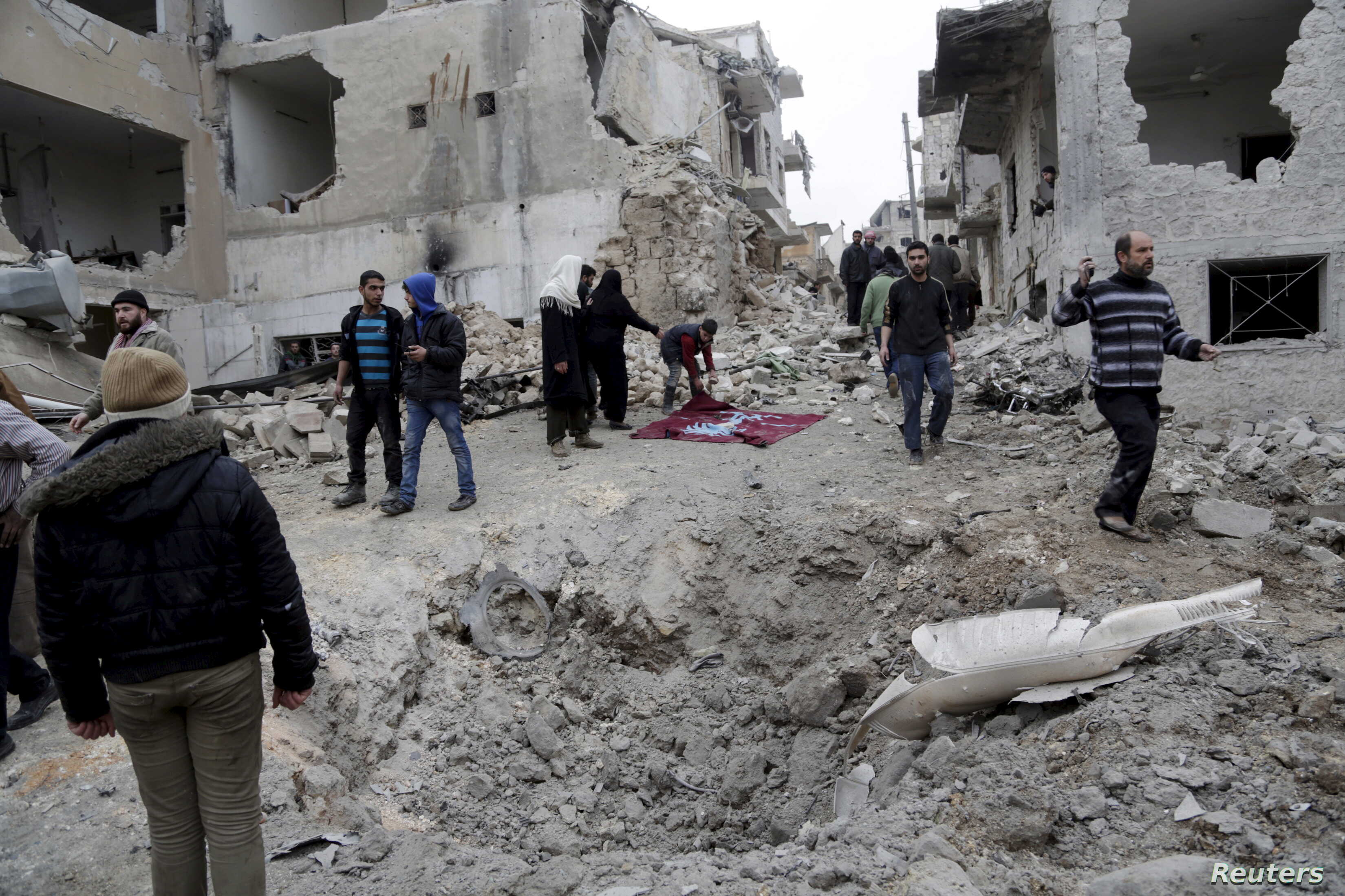 FILE - Residents inspect a crater at a site hit by what activists said were three consecutive air strikes carried out by the Russian air force, the last which hit an ambulance, in the rebel-controlled area of Maaret al-Numan town in Idlib province, S...