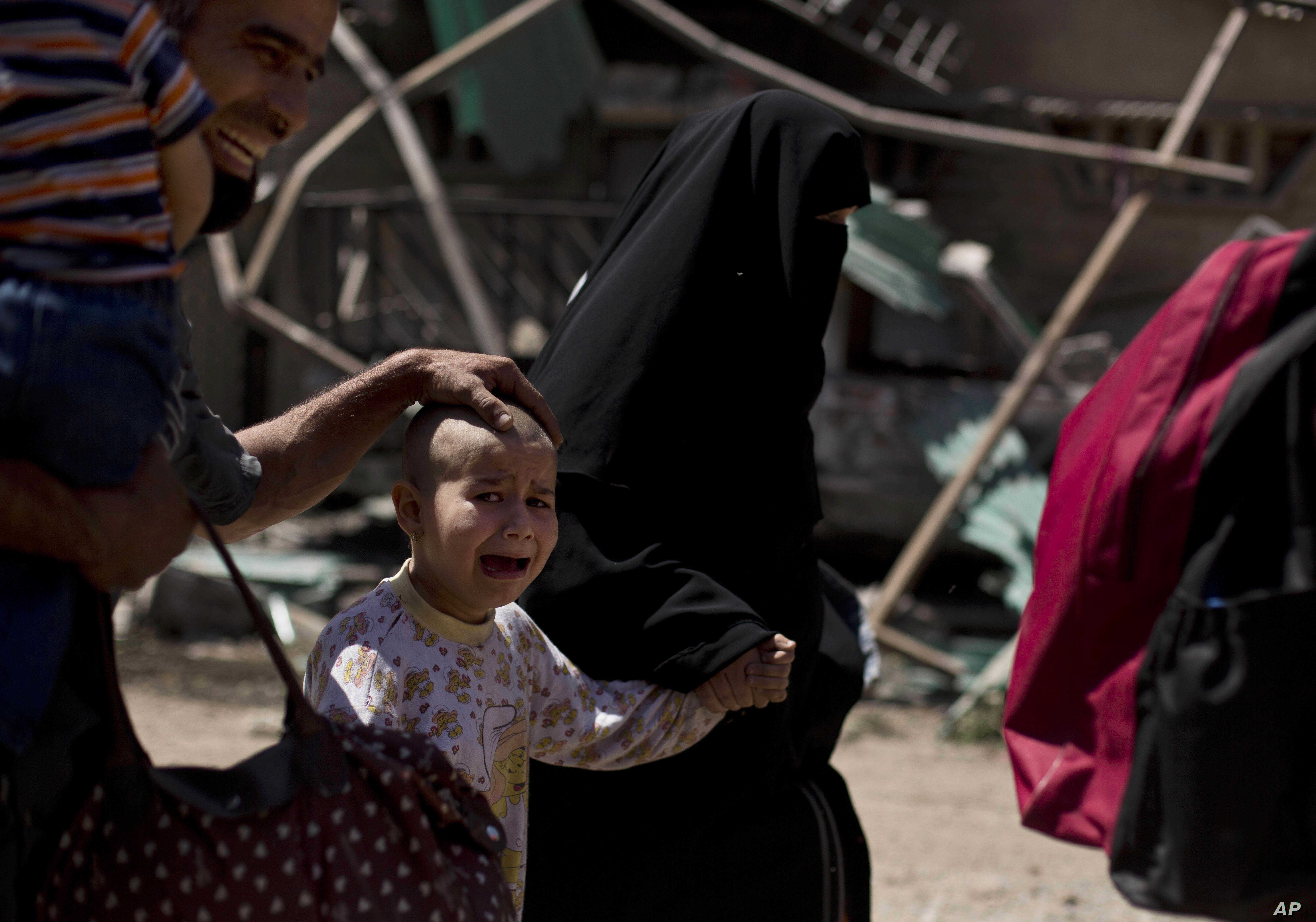 A girl with a shaved head and her father cry as the family flees the al-Rifai neighborhood while Iraqi special forces battle Islamic State militants in western Mosul, Iraq, May 17, 2017.