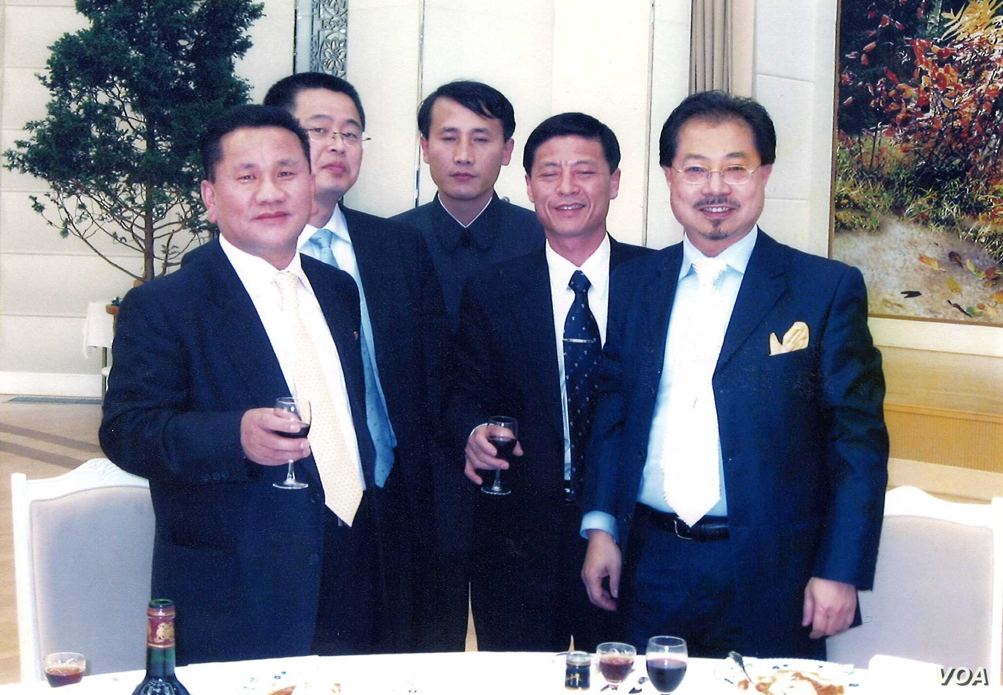 Ri Jong Ho, left, poses with Chinese investment tycoon Sam Pa, right, and others at a banquet hall in Pyongyang in January 2007.