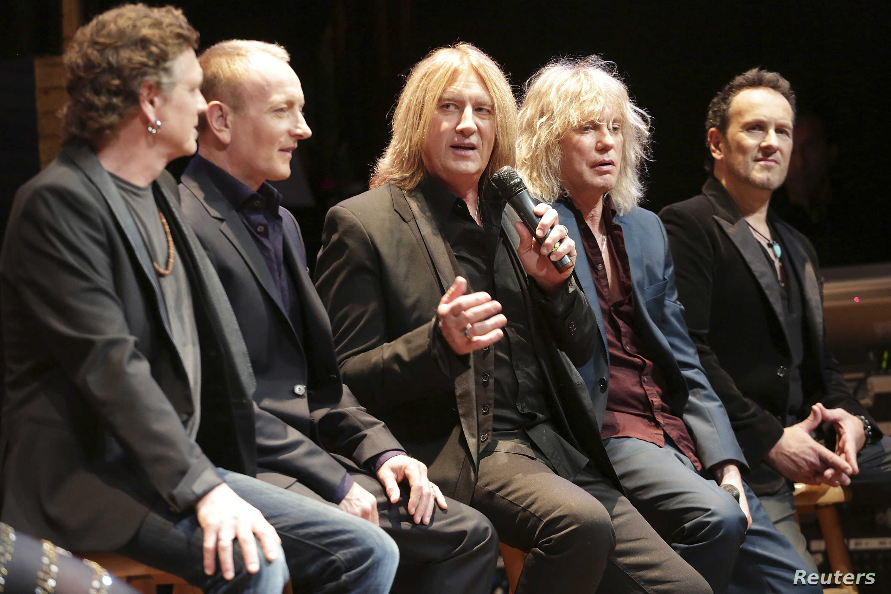 FILE - Rick Allen (L-R), Phil Collen, Joe Elliott, Rick Savage and Vivian Campbell of Def Leppard speak on stage at the House of Blues in West Hollywood, California, March 17, 2014.