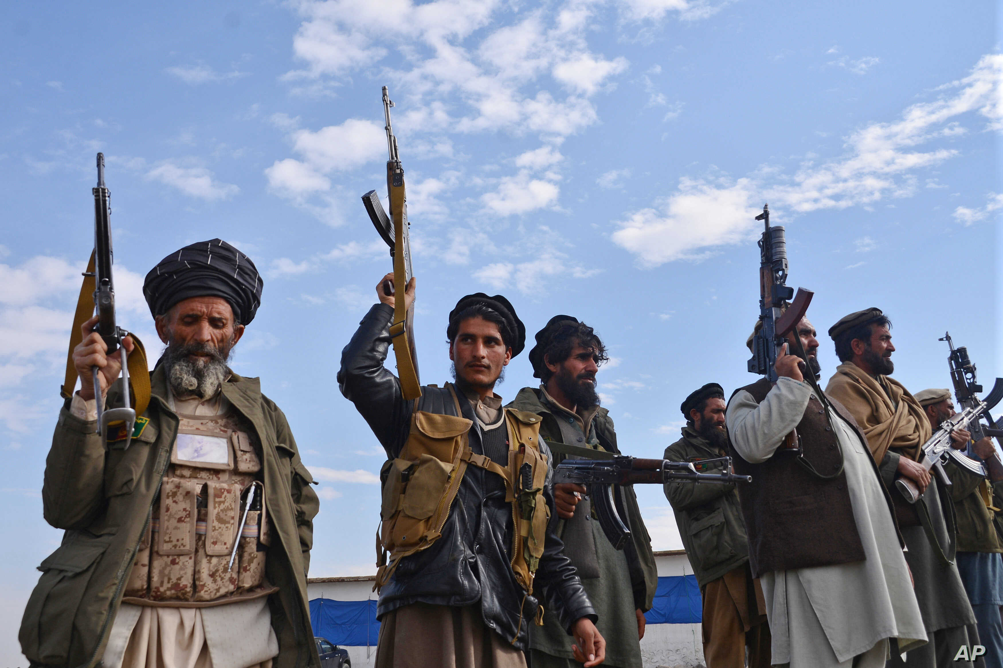 Afghan militiamen raise their weapons as they stand guard in the Achin district of Nangarhar province, Afghanistan, Dec. 27, 2015.