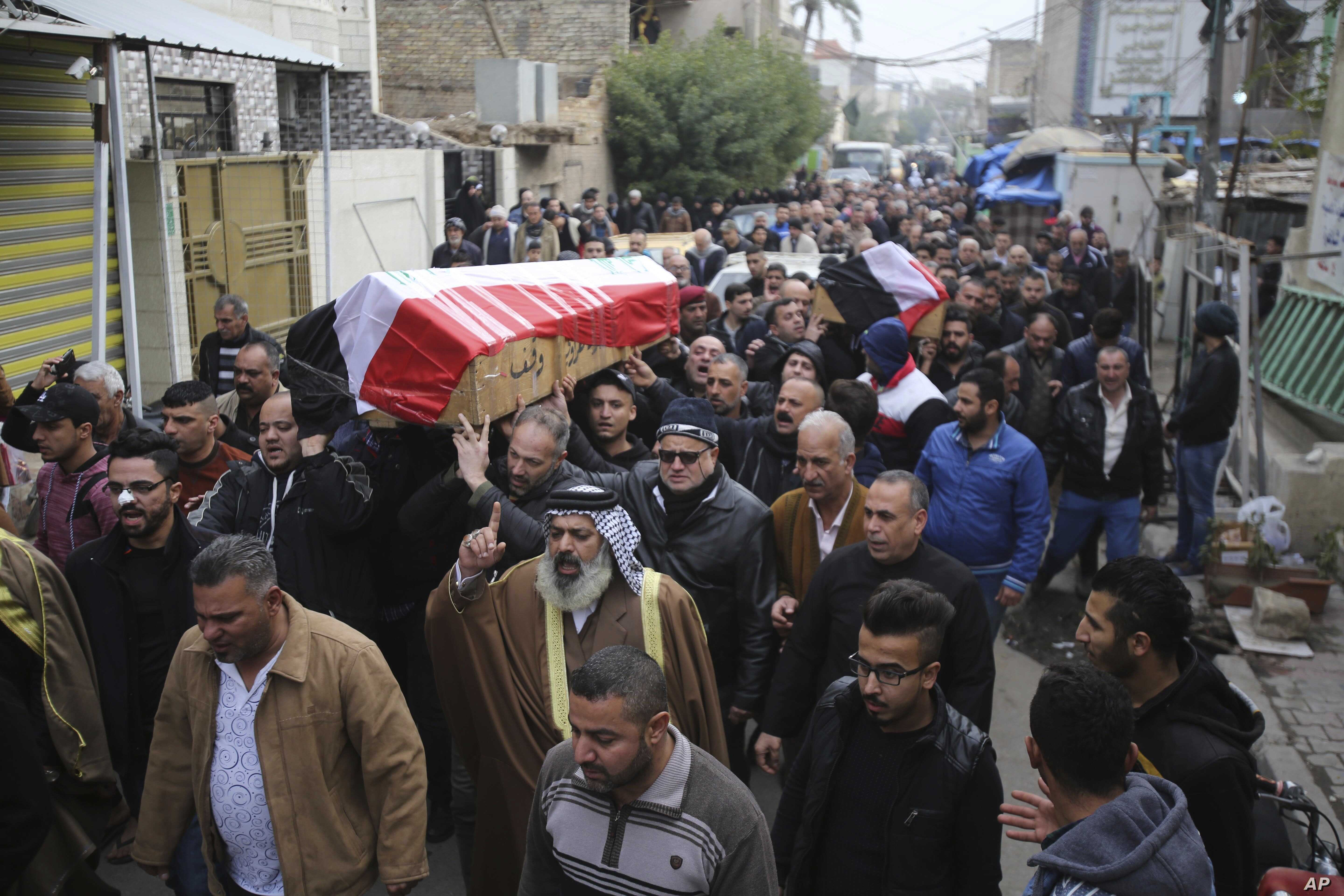 Mourners carry the Iraqi flag-draped coffins of bomb victims Arif Muhanad, 36, and his son, Muhanad, 8, during their funeral procession in Baghdad, Iraq, Dec 31, 2016. A pair of bomb blasts targeting a market Saturday in central Baghdad killed and wo...