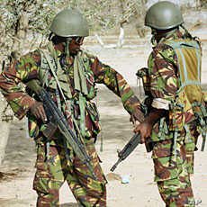 Kenyan soldiers talk as they prepare to advance near Liboi in Somalia on October 18, 2011