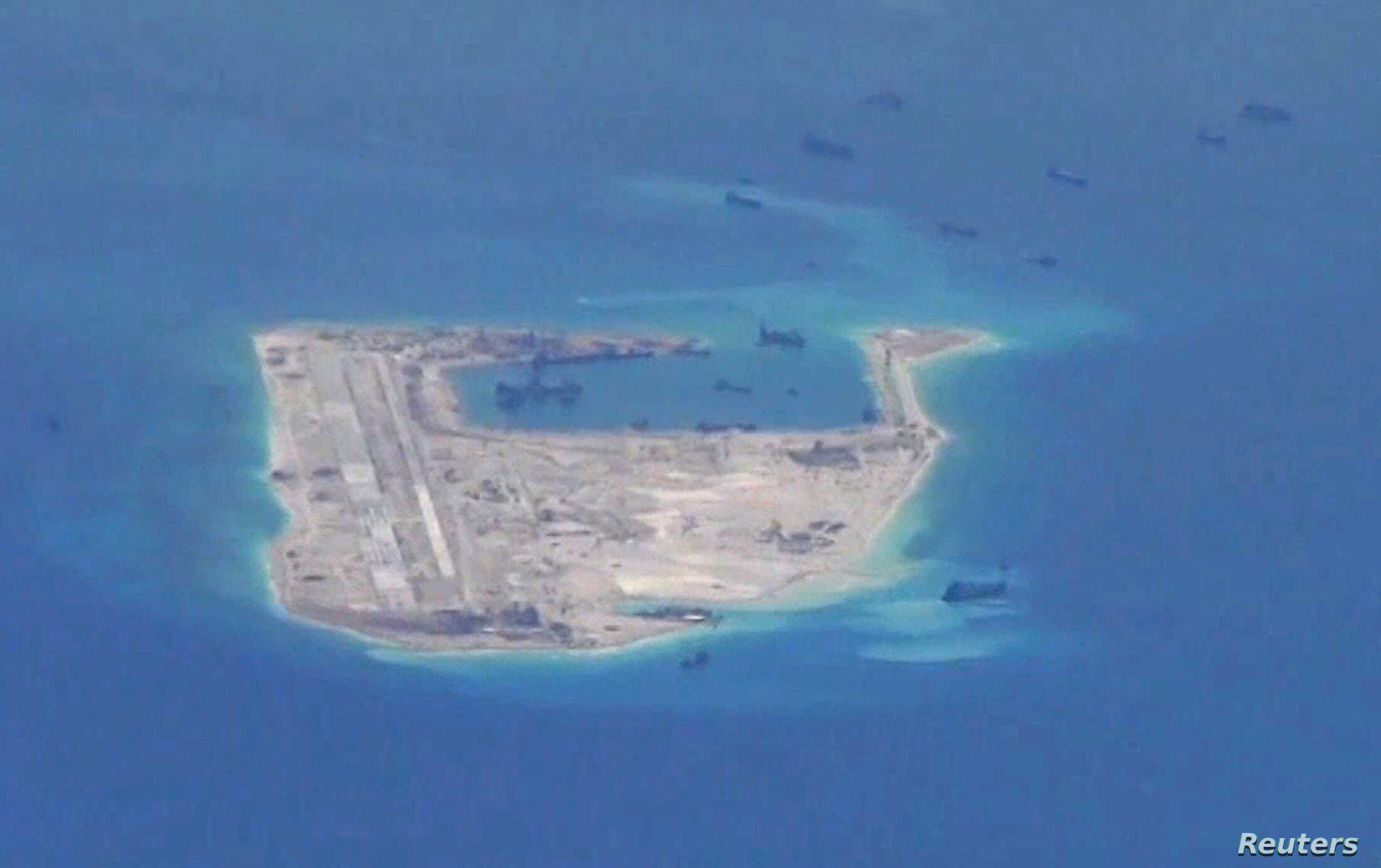 FILE PHOTO - Chinese dredging vessels are purportedly seen in the waters around Fiery Cross Reef in the disputed Spratly Islands in the South China Sea in this still image taken by a P-8A Poseidon surveillance aircraft, May 21, 2015.