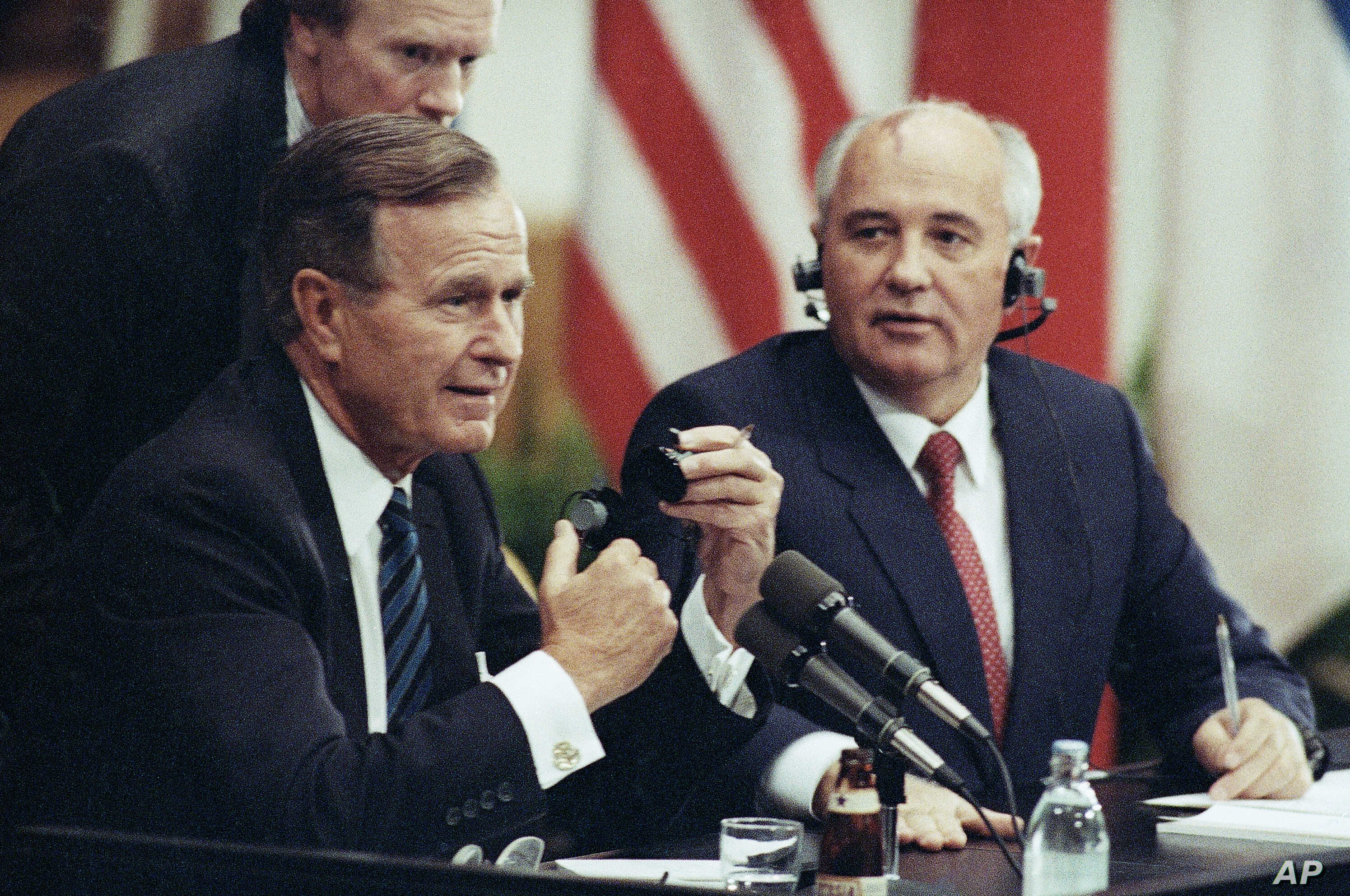 U.S. President George H. Bush works to get an earphone plug from his ear as Soviet President Mikhail Gorbachev laughs during their joint news conference, Sunday, Sept. 9, 1990 in Helsinki. (AP Photo/Liu Heung Shin)